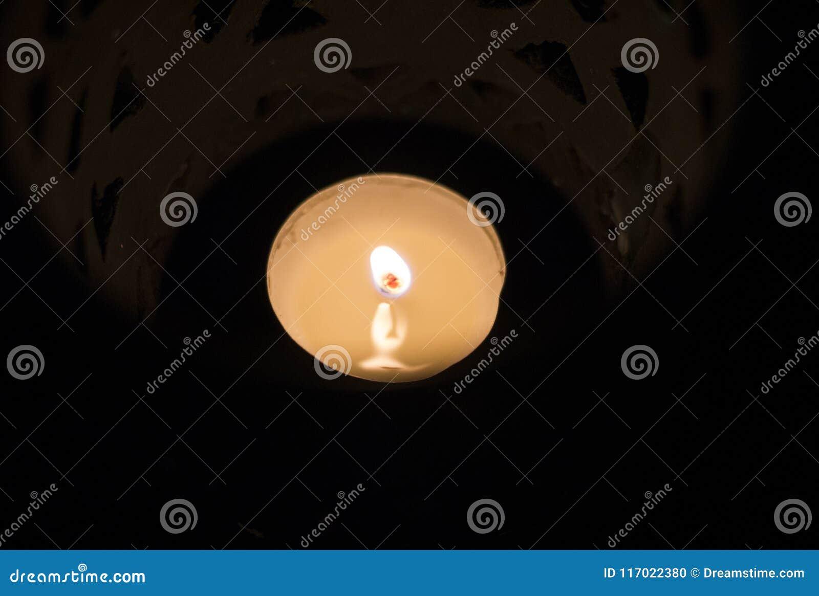 Να καταπλήξει κοντά επάνω των αναμμένων κεριών σε έναν όμορφο μπλε κάτοχο κεριών