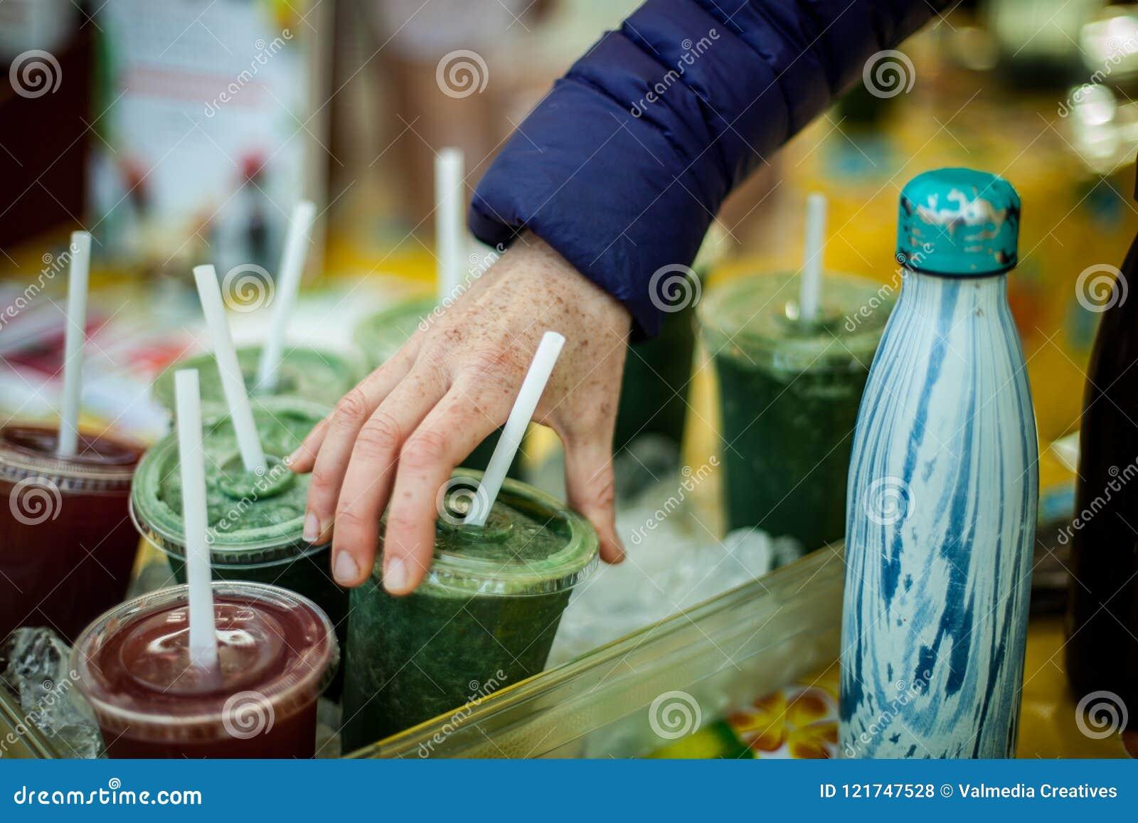 Να μαζεψει με το χέρι επάνω έναν κρύο πράσινο καταφερτζή στην αγορά του αγρότη