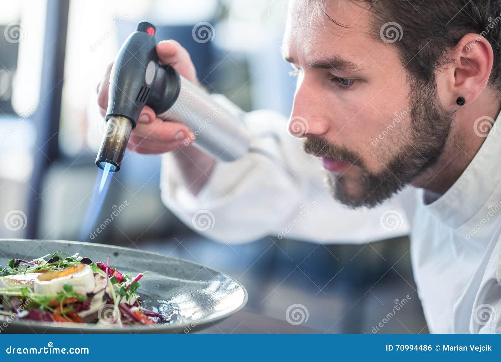 να προετοιμαστεί τροφίμω& Ο μάγειρας φλεγόταν χρησιμοποιώντας το πιστόλι πυροβόλων όπλων Flambé Φυτική σαλάτα αρχιμαγείρων flamb