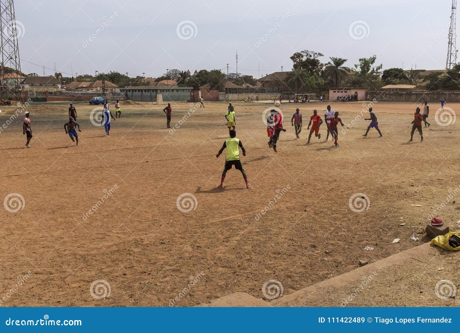 Νεαροί άνδρες που παίζουν το ποδόσφαιρο σε έναν τομέα ρύπου στην πόλη του Μπισσάου, στη Γουινέα-Μπισσάου