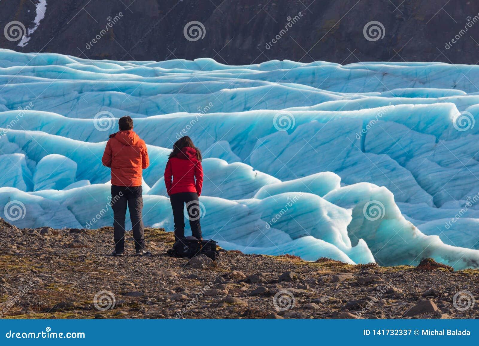 Νεαρός άνδρας και γυναίκα που στέκονται πριν του όμορφου τοπίου βραδιού του εθνικού πάρκου Vatnajokull παγετώνων Skaftafell στην