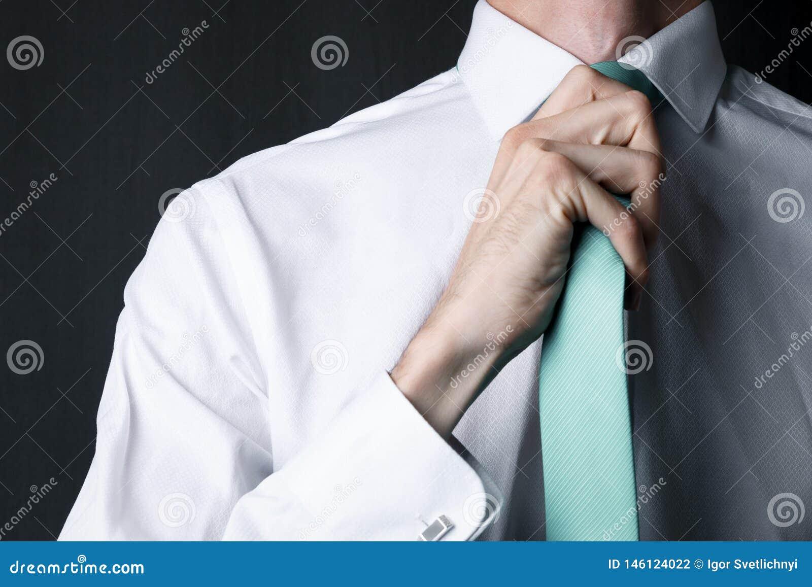 Νεαρός άνδρας κινηματογραφήσεων σε πρώτο πλάνο σε ένα άσπρο πουκάμισο με μια μέντα χρώματος δεσμών