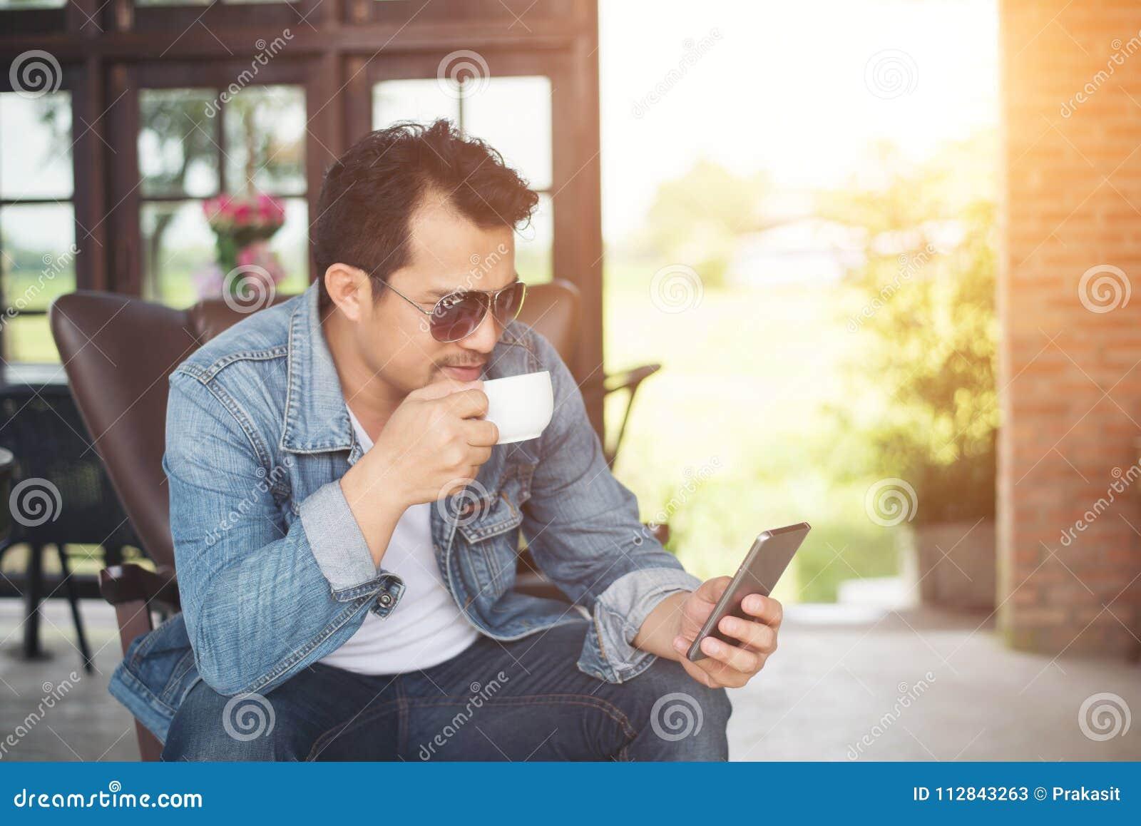 Νεαρός άνδρας με τη χαλάρωση χαμόγελου smartphone στον καφέ