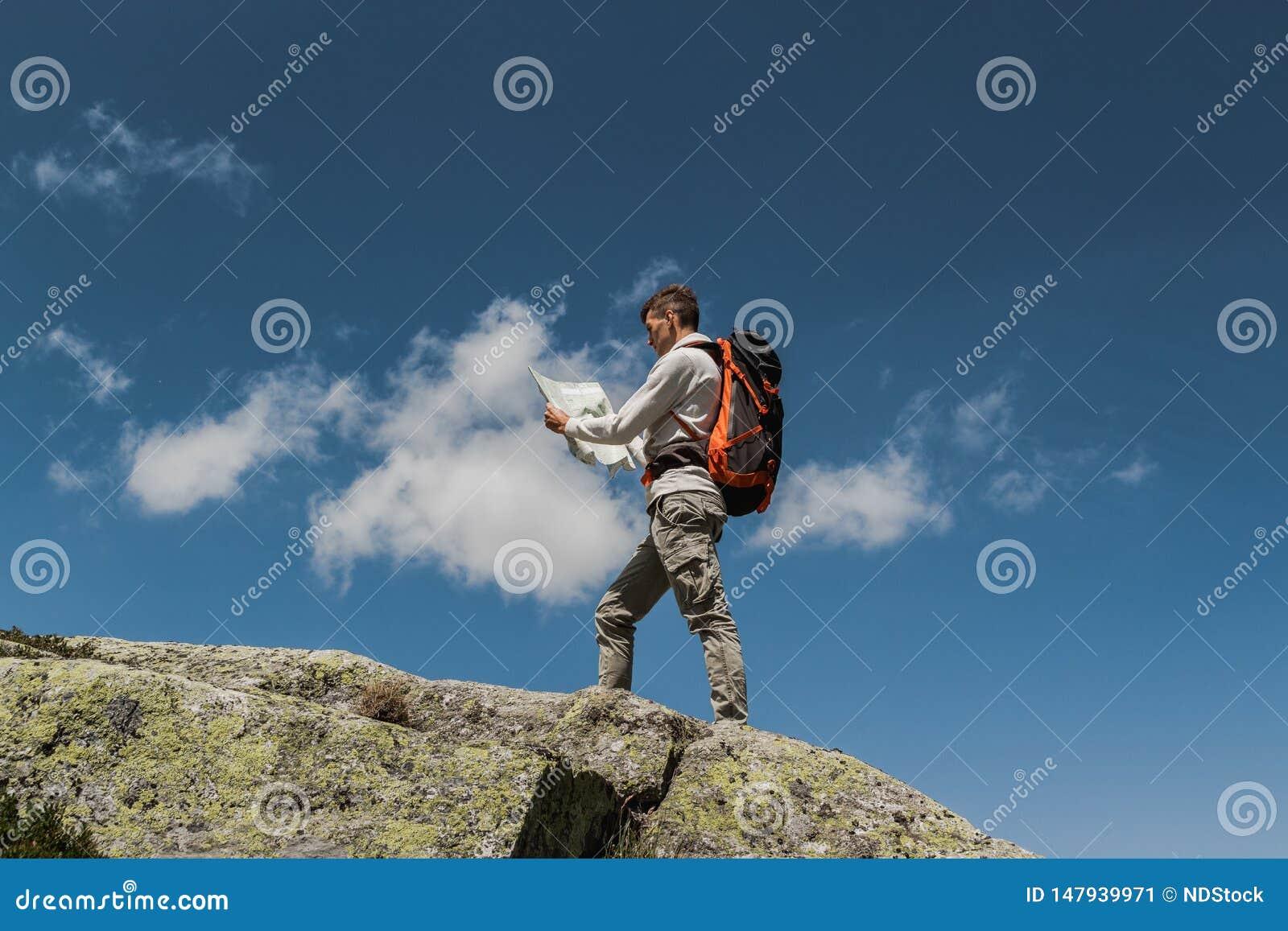 Νεαρός άνδρας με το μεγάλο σακίδιο πλάτης που περπατά για να φθάσει στην κορυφή του βουνού κατά τη διάρκεια μιας ηλιόλουστης ημέρ