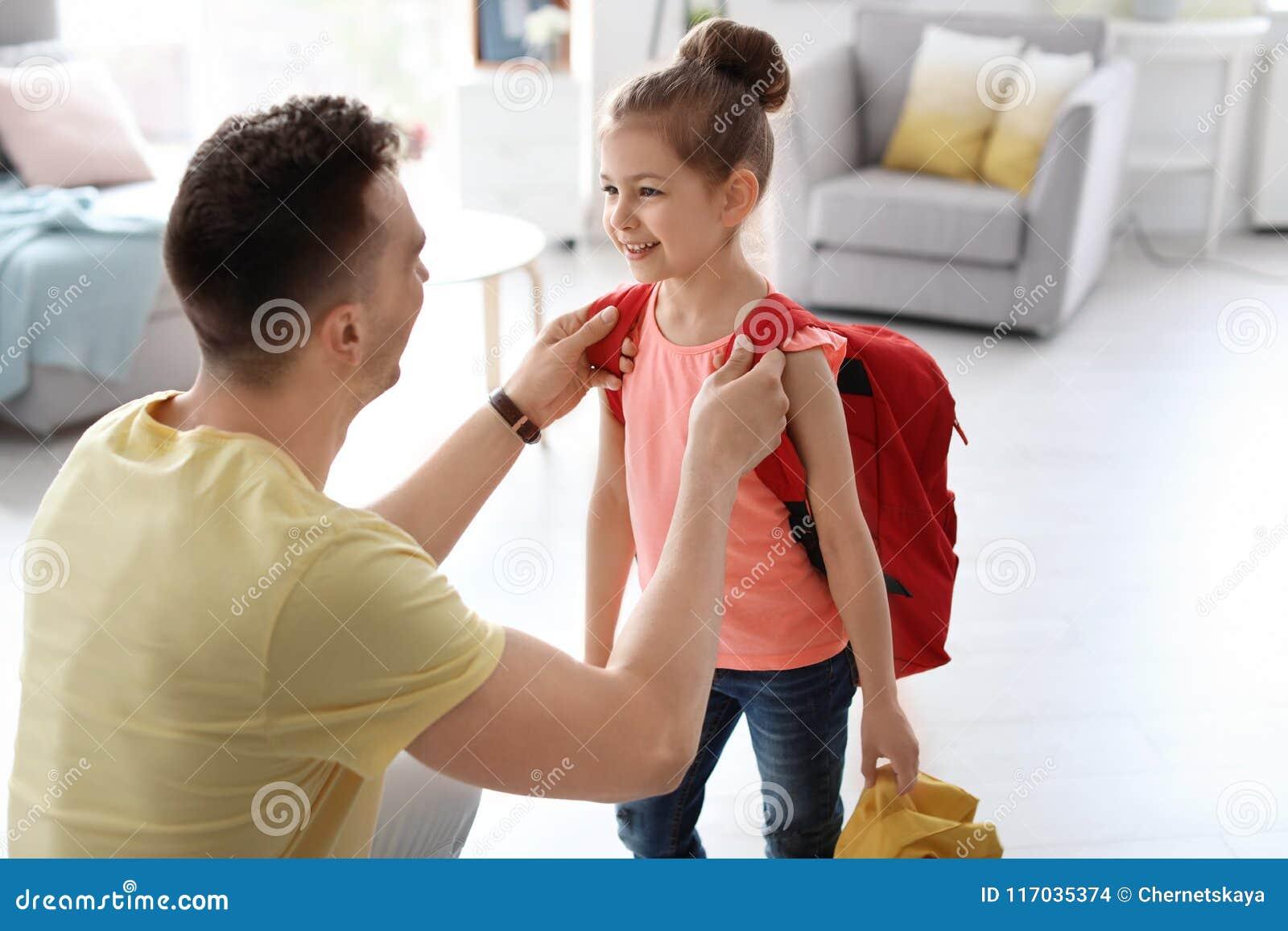 Νεαρός άνδρας που βοηθά το μικρό παιδί του να πάρει έτοιμο για το σχολείο