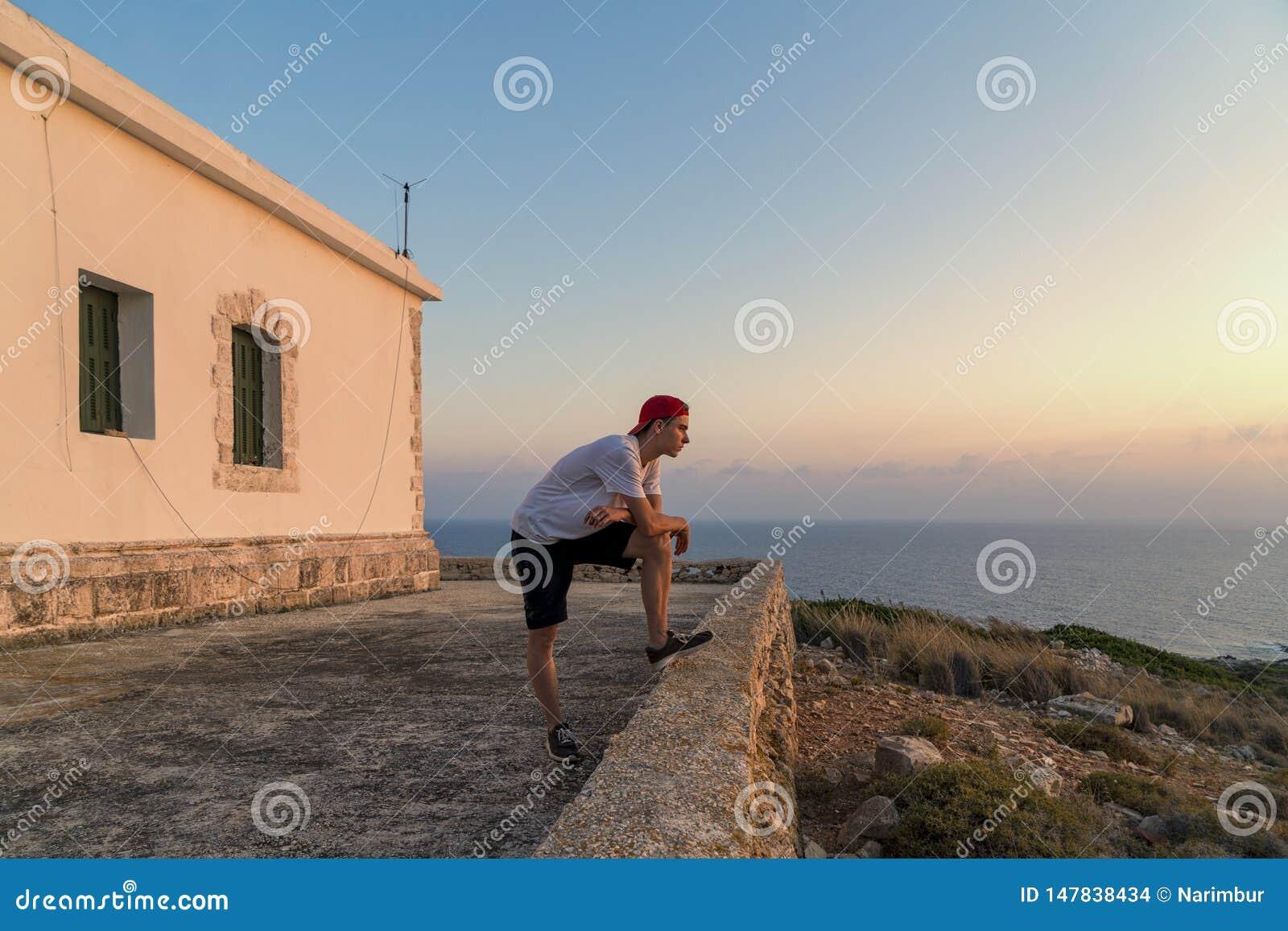Νεαρός άνδρας, που εξετάζει το ηλιοβασίλεμα