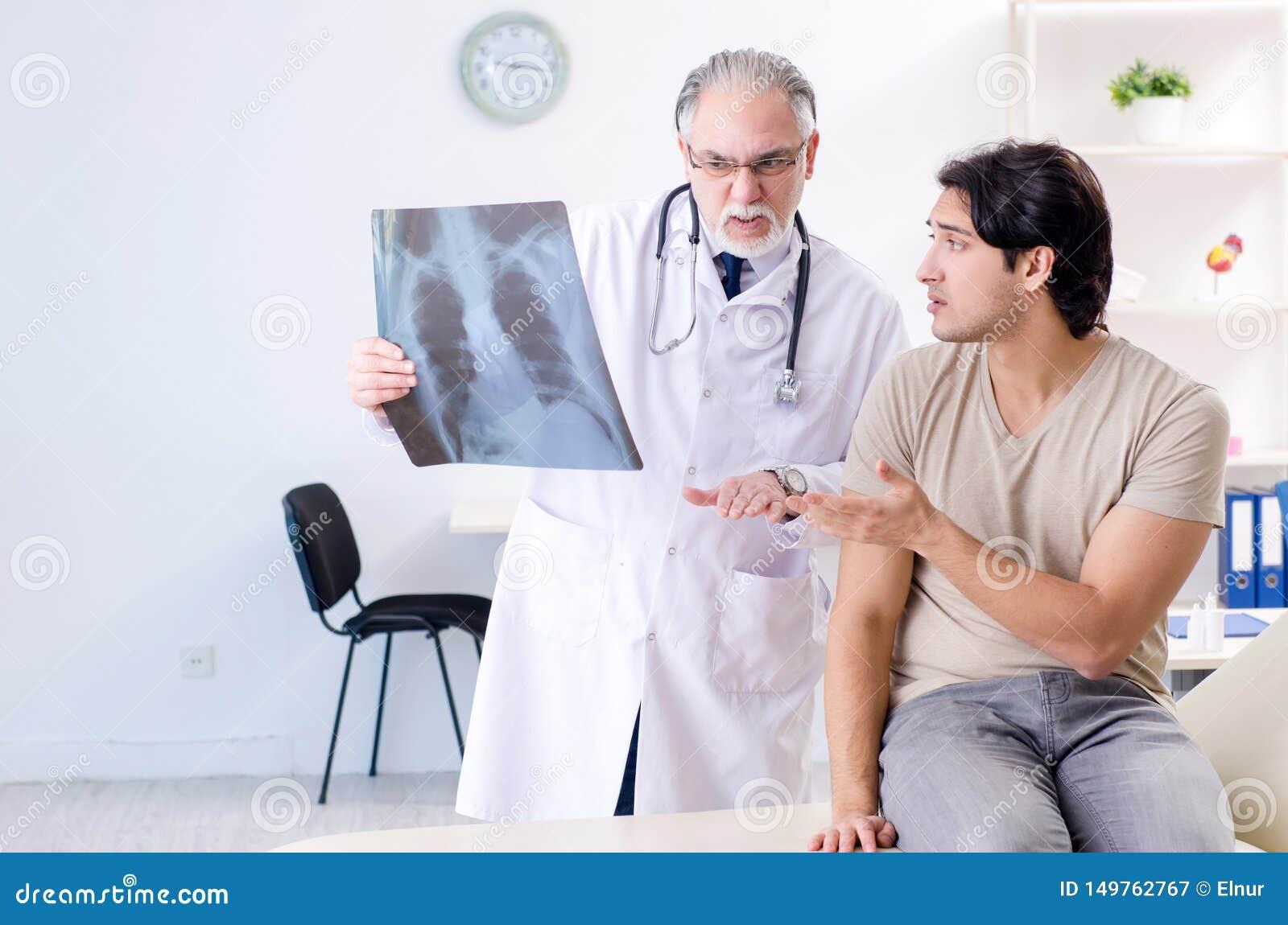 Νεαρός άνδρας που επισκέπτεται τον παλαιό αρσενικό ακτινολόγο γιατρών