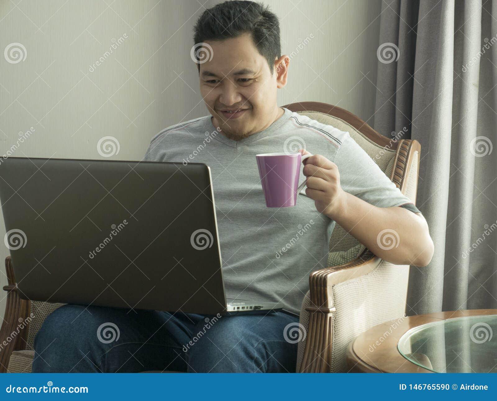 Νεαρός άνδρας που εργάζεται στο σπίτι στο lap-top του, έκφραση χαμόγελου