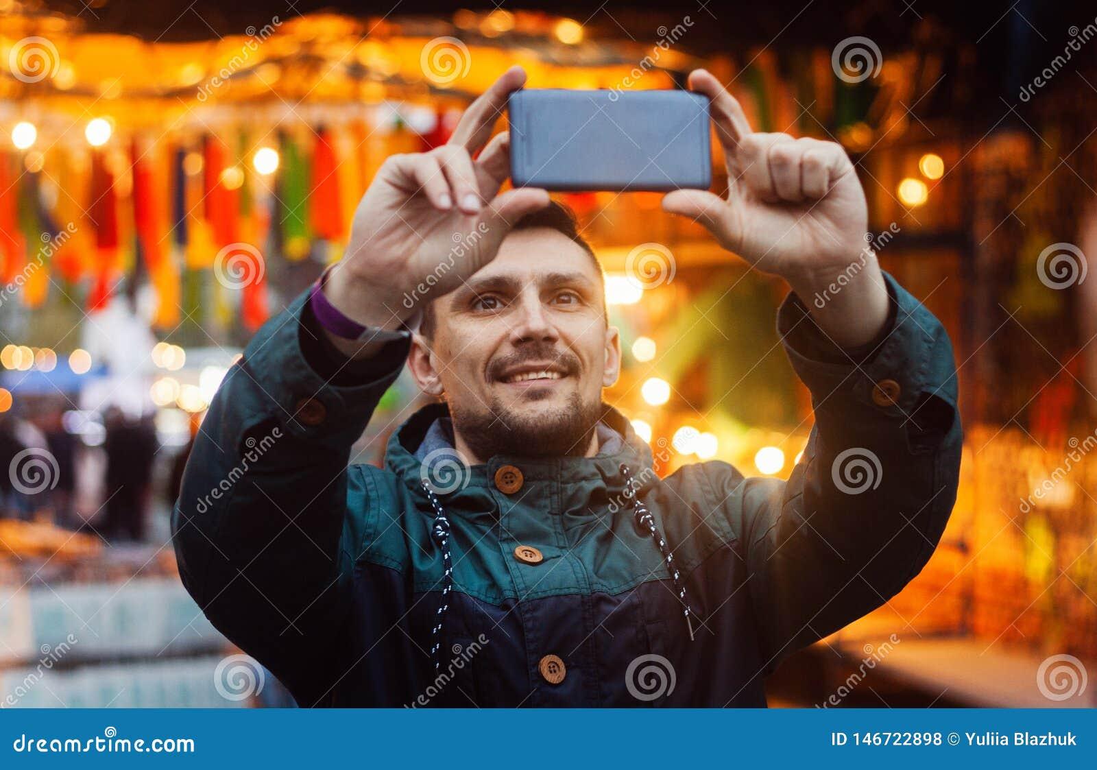 Νεαρός άνδρας που παίρνει τη φωτογραφία με το τηλέφωνο στην οδό που διακοσμείται με τις ζωηρόχρωμες σημαίες