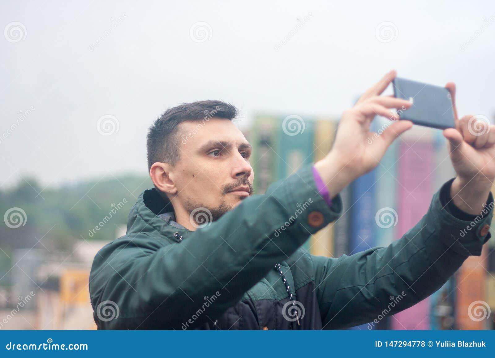 Νεαρός άνδρας που παίρνει τη φωτογραφία με το τηλέφωνό του στη στέγη