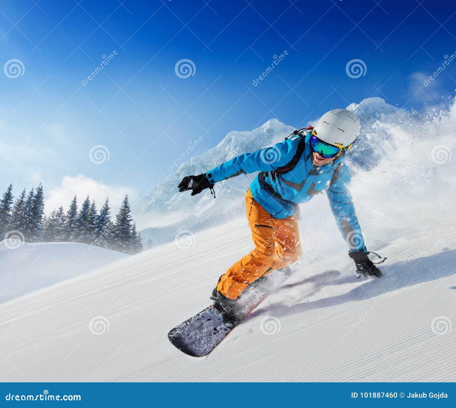 Νεαρός άνδρας snowboarder που μειώνει την κλίση στα αλπικά βουνά