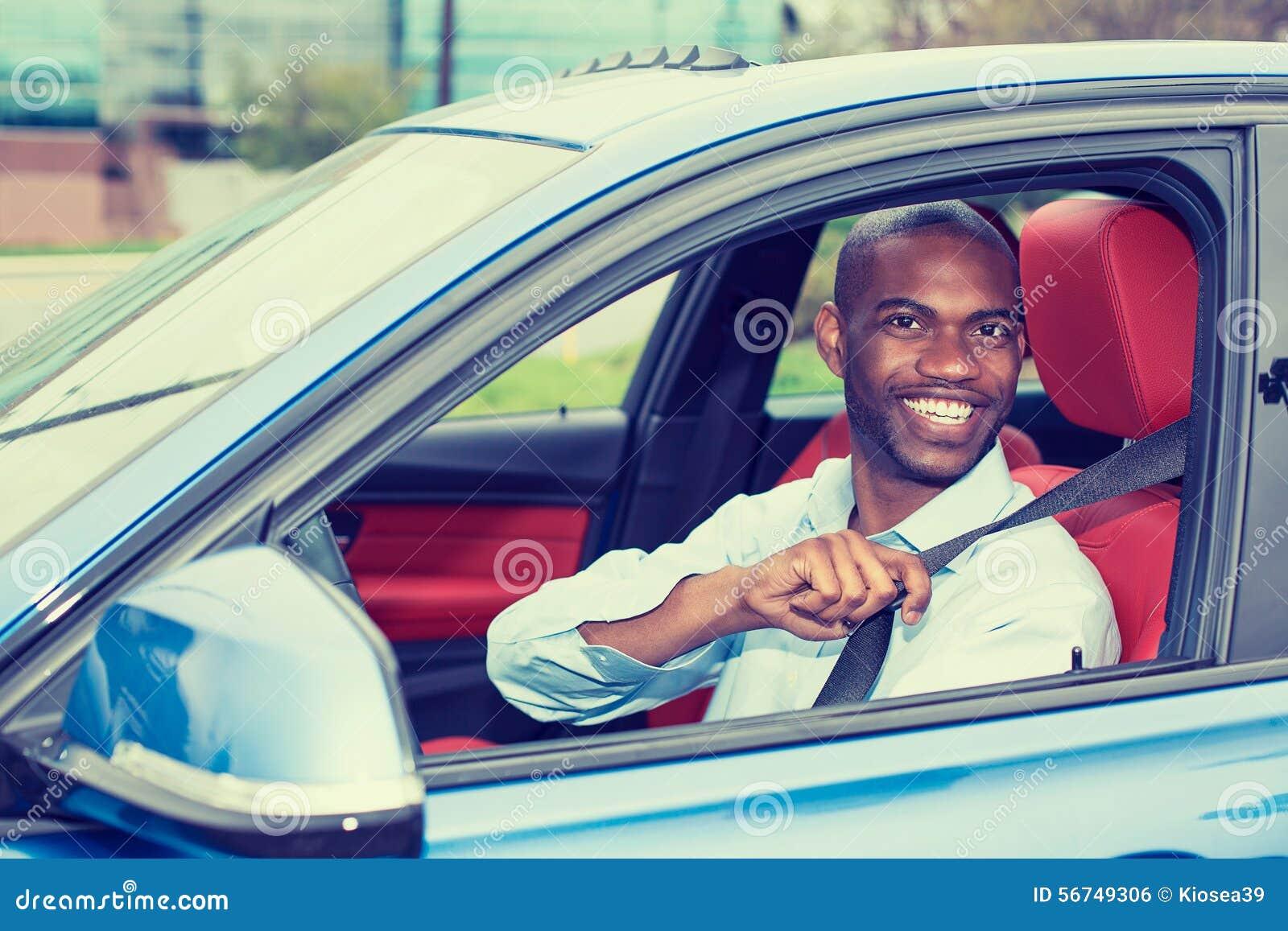 Νεαρός άνδρας οδηγών αυτοκινήτων που φορά τη ζώνη ασφάλειας που οδηγεί το νέο αυτοκίνητο