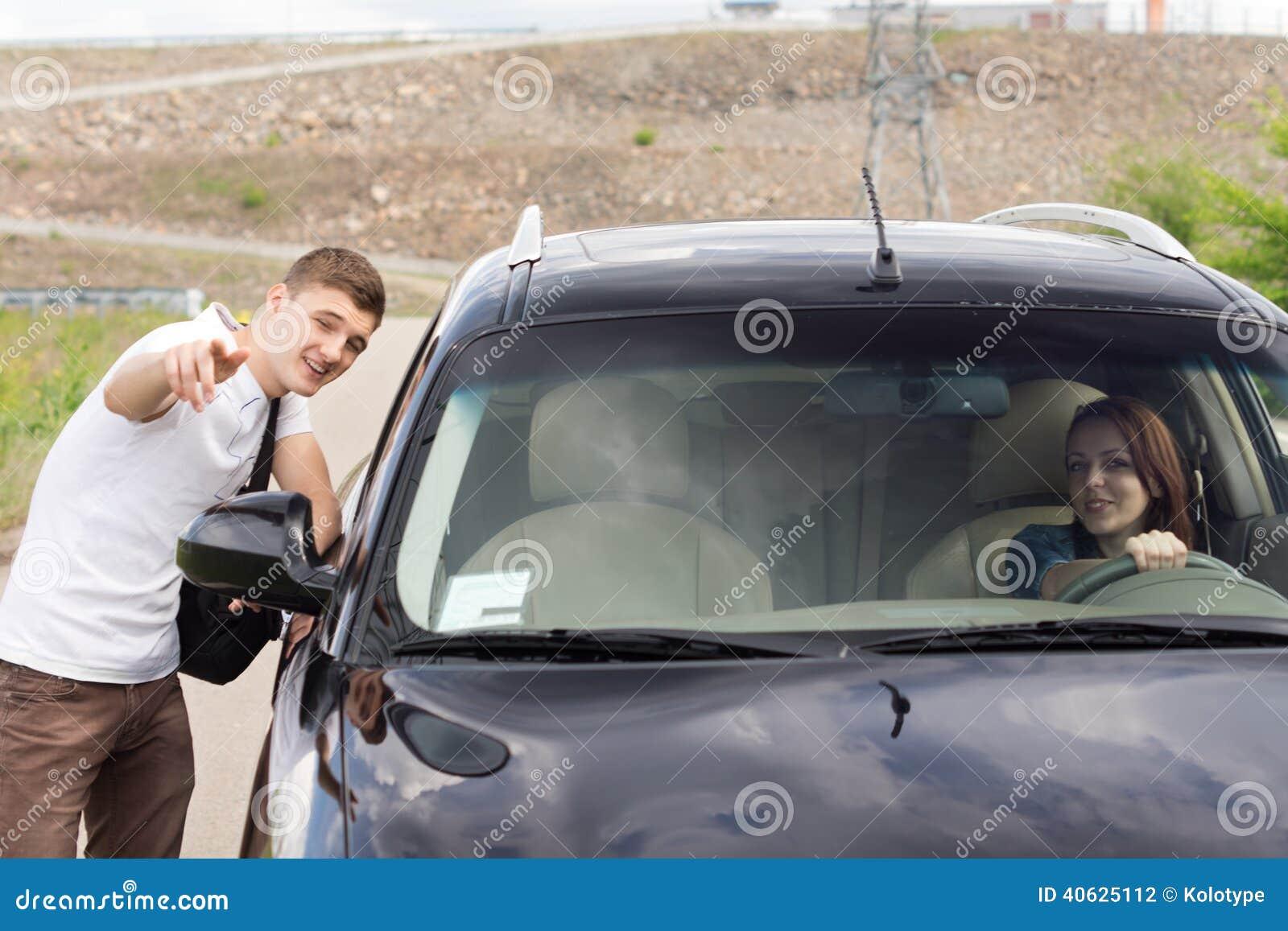 Νεαρός άνδρας που δίνει τις κατευθύνσεις σε έναν οδηγό γυναικών