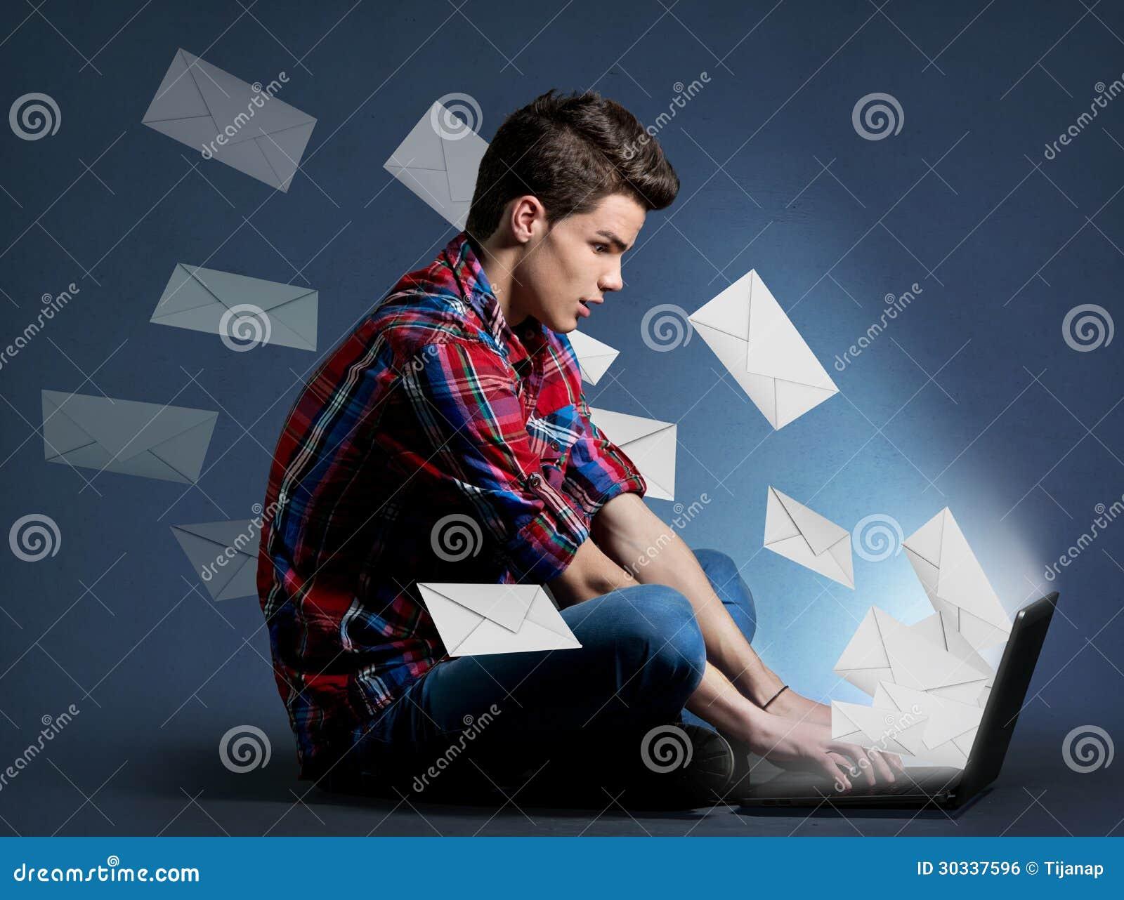Νεαρός άνδρας που λαμβάνει τους τόνους των μηνυμάτων στο lap-top