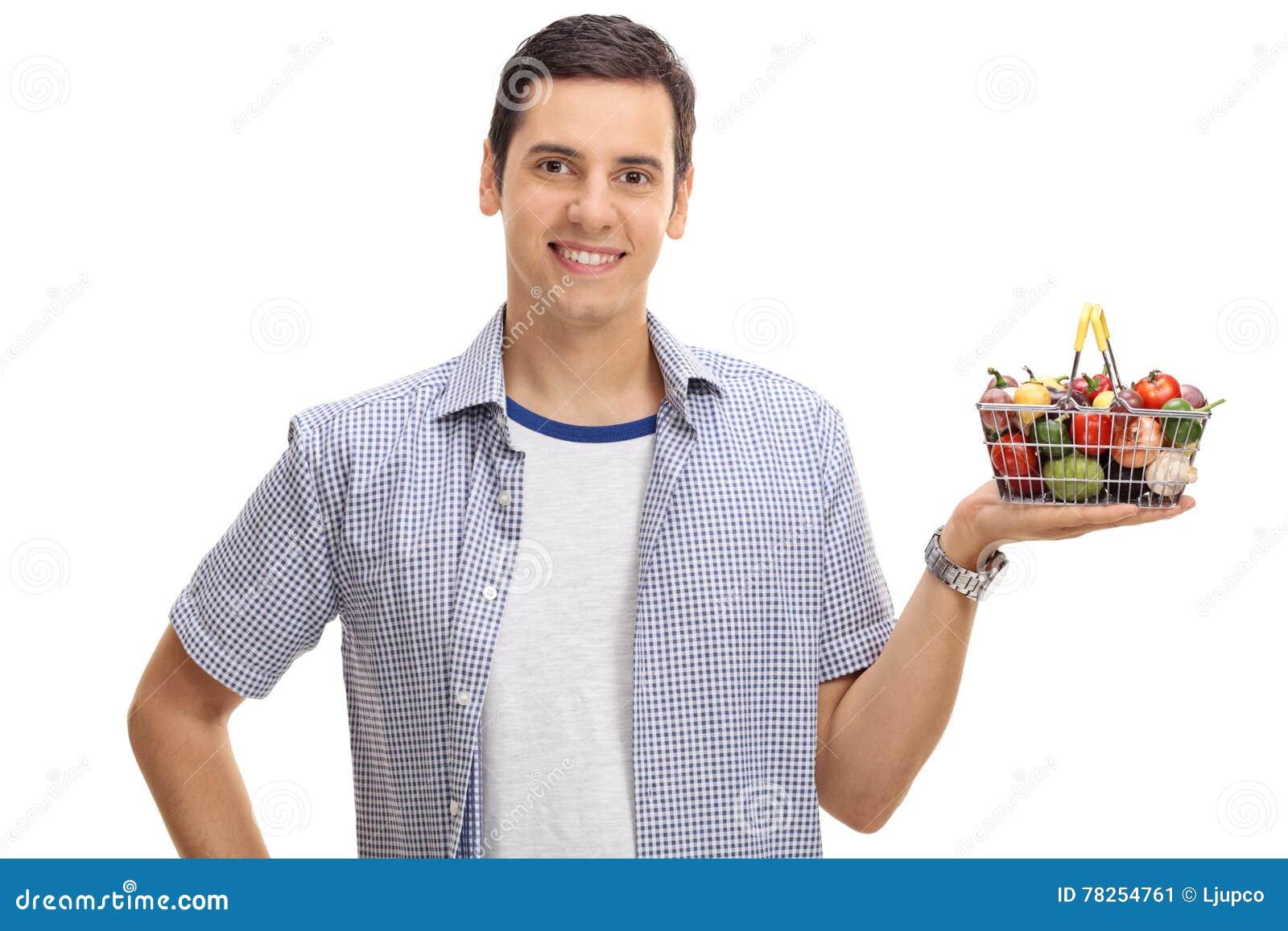 Νεαρός άνδρας που κρατά ένα μικρό καλάθι αγορών