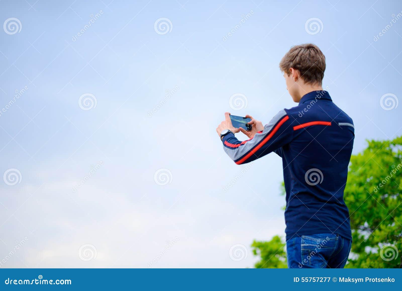 Νεαρός άνδρας που παίρνει τη φωτογραφία τοπίων που χρησιμοποιεί το κινητό έξυπνο τηλέφωνο