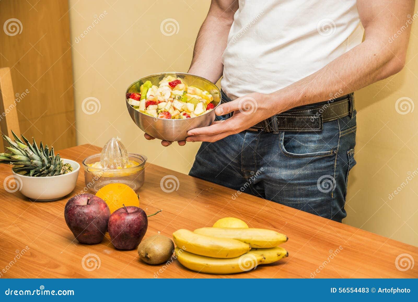 Download Νεαρός άνδρας που προετοιμάζει μια σαλάτα ή έναν καταφερτζή φρούτων Στοκ Εικόνα - εικόνα από τακτοποίηση, σφαιριστών: 56554483