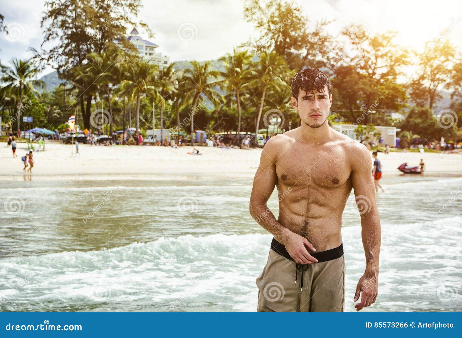 Νεαρός άνδρας που στέκεται στην άκρη του ωκεανού