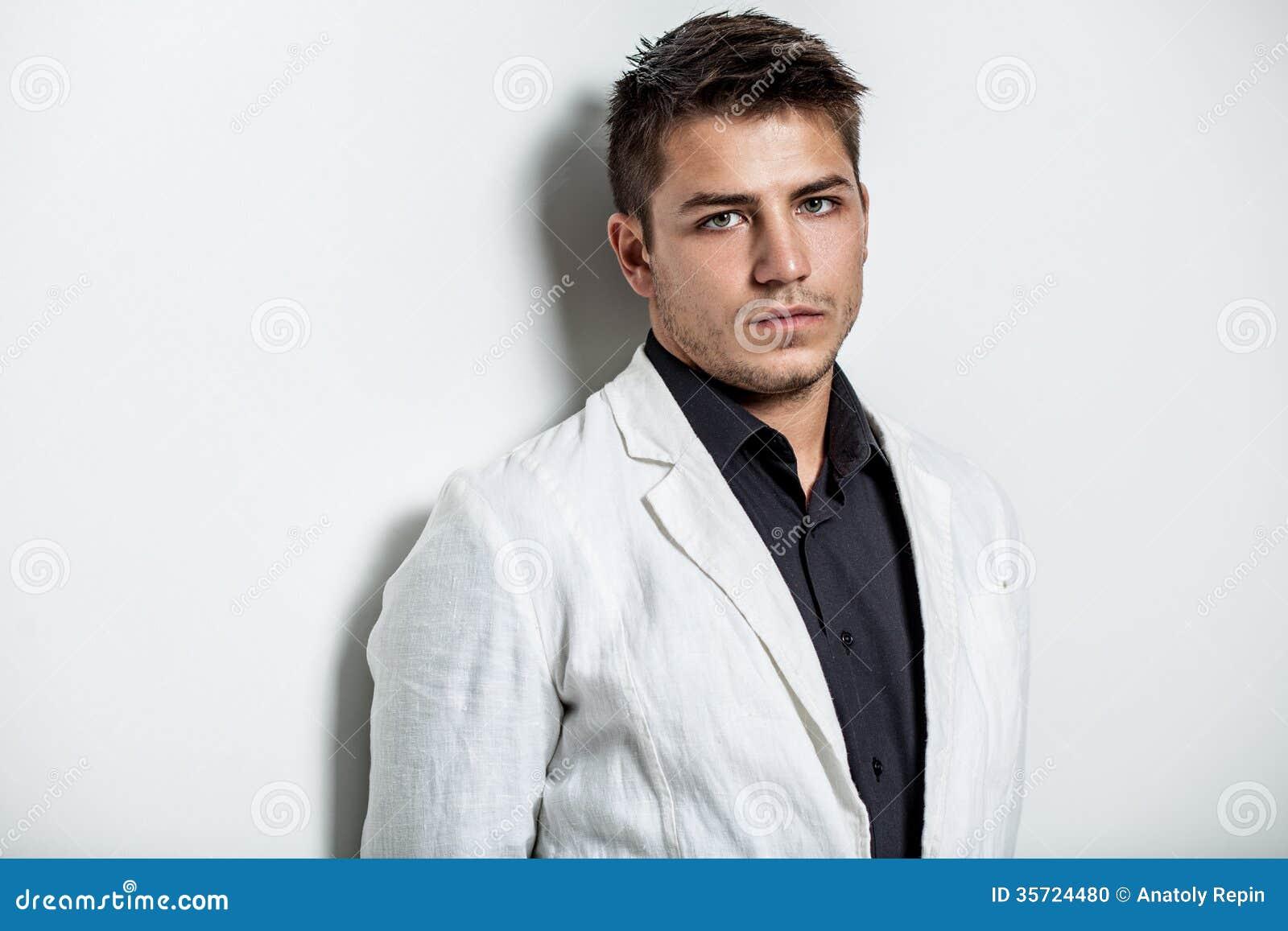 Νεαρός άνδρας που φορά το άσπρο κοστούμι
