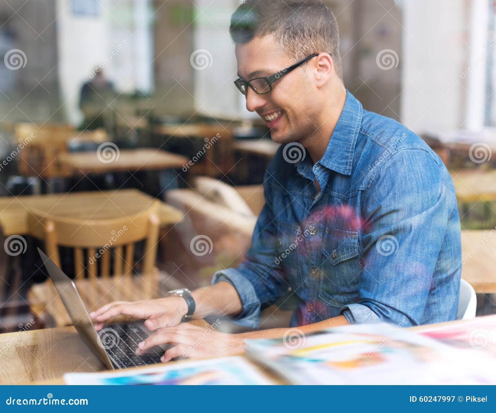 Νεαρός άνδρας που χρησιμοποιεί το lap-top στον καφέ