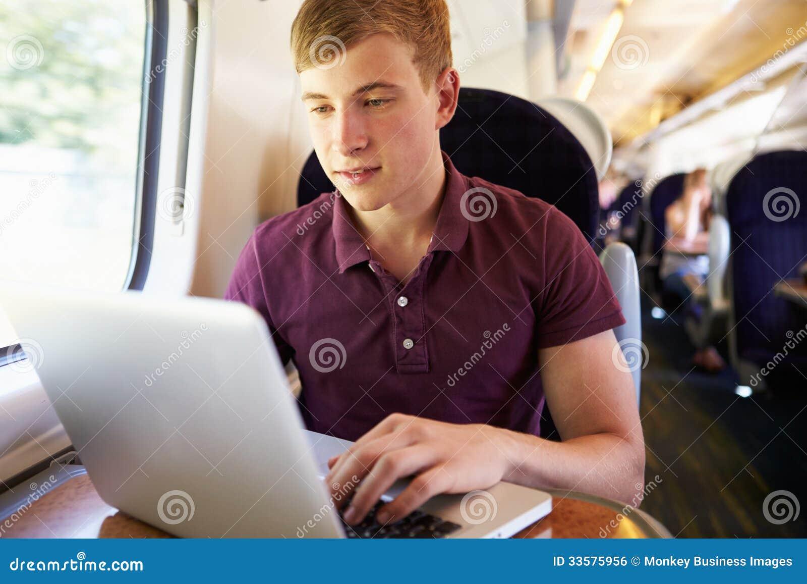Νεαρός άνδρας που χρησιμοποιεί το lap-top στο ταξίδι τραίνων