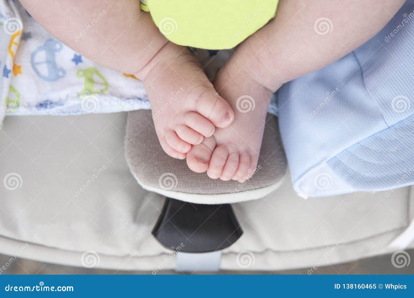 Νεογέννητα chubby πόδια μωρών στο αυτοκίνητο μωρών ι-μεγέθους πέρα από τον περιπατητή