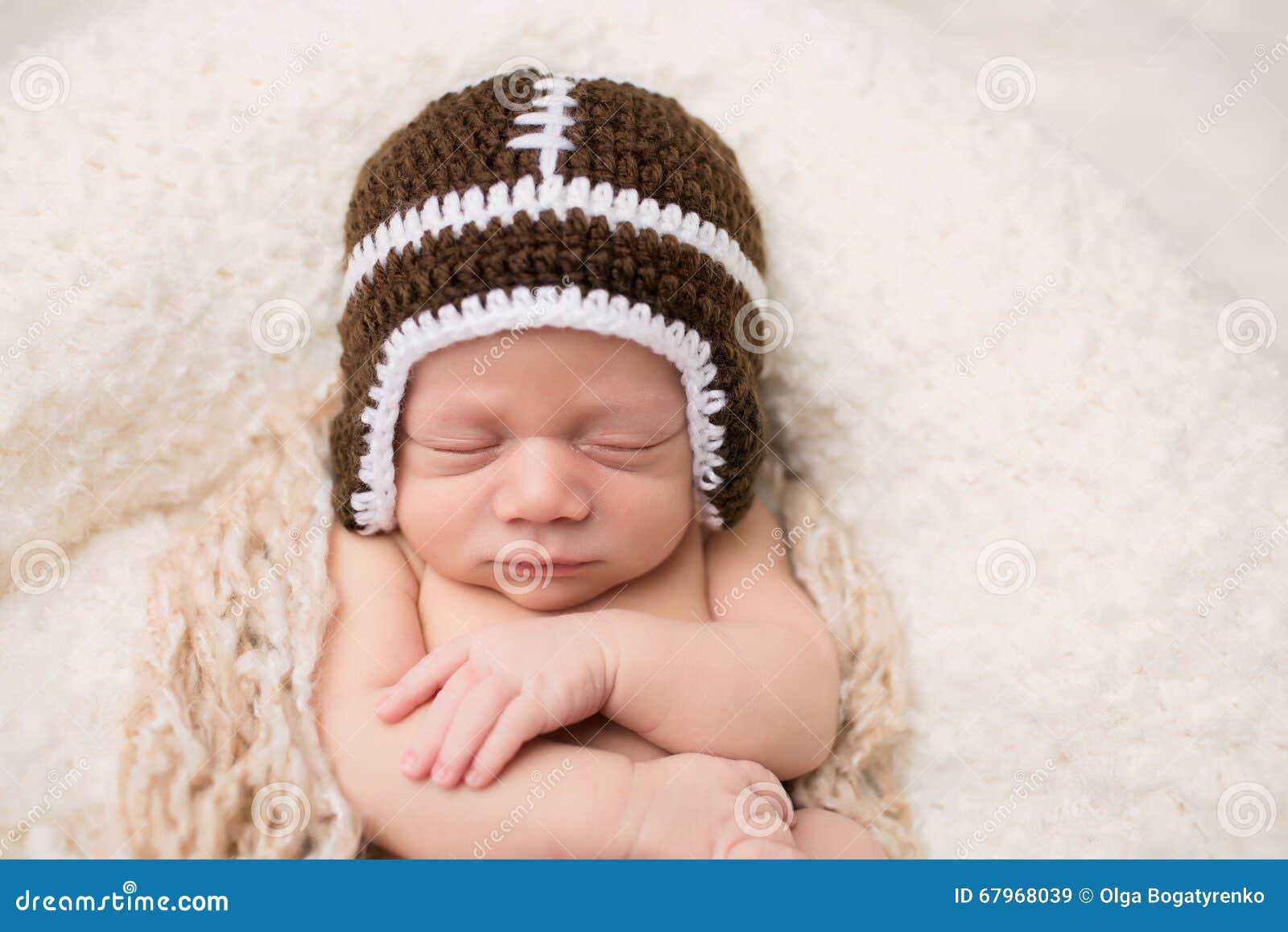Νεογέννητος ύπνος μωρών στο καπέλο ποδοσφαίρου