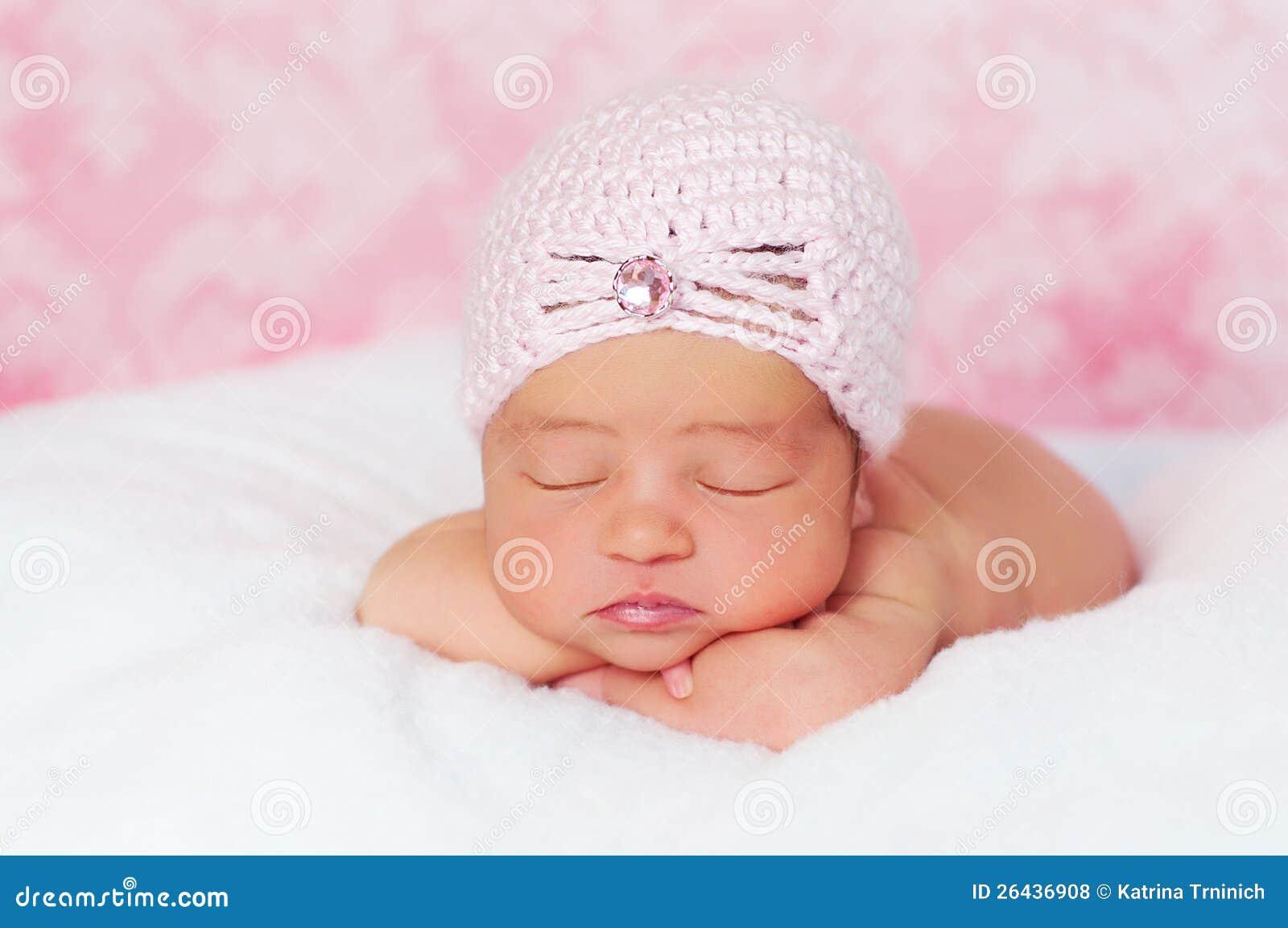 Νεογέννητο κοριτσάκι που φορά ένα ρόδινο καπέλο ύφους πτερυγίων