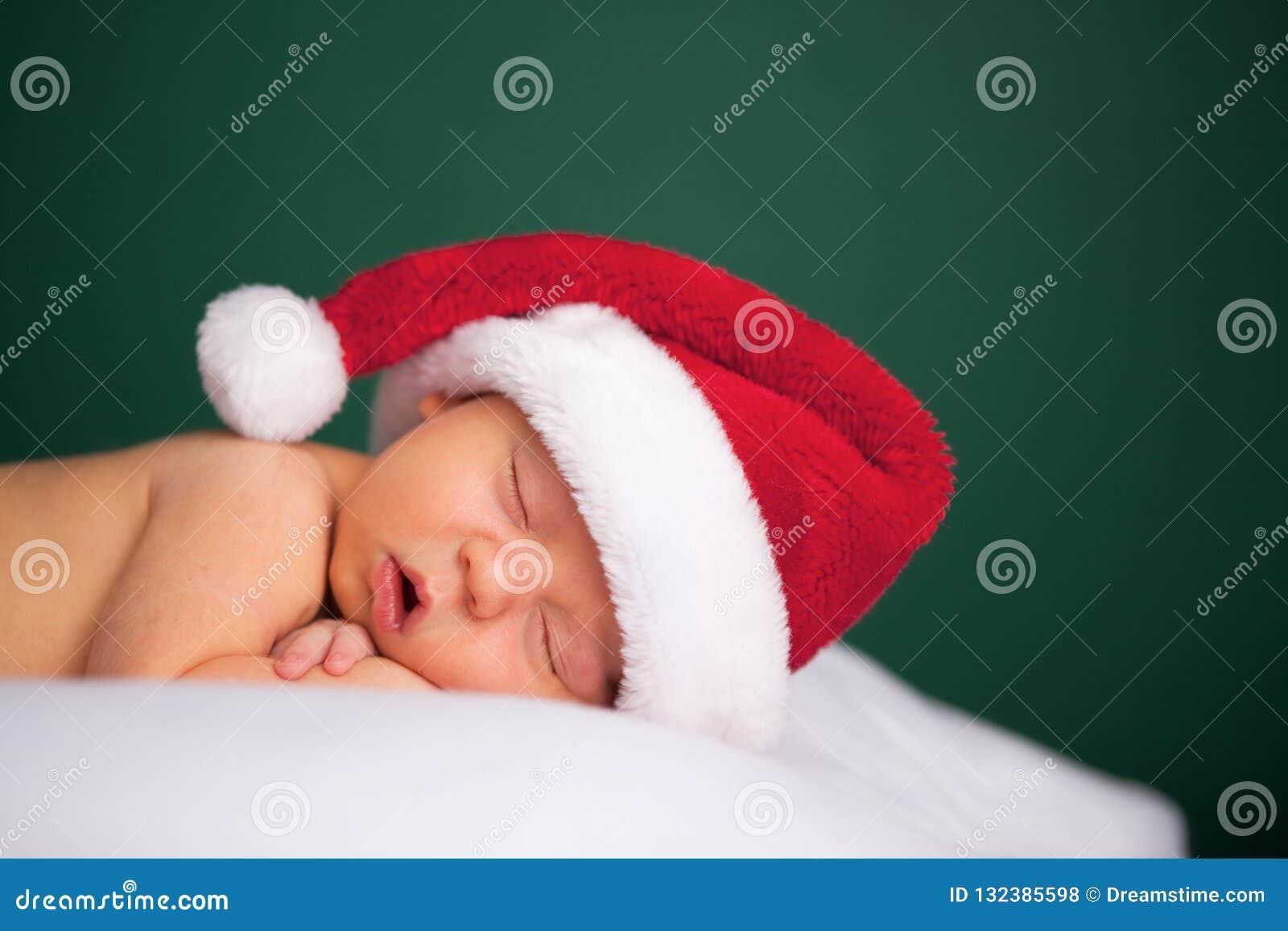 Νεογέννητο μωρό Χριστουγέννων που φορά το καπέλο και τον ύπνο Santa