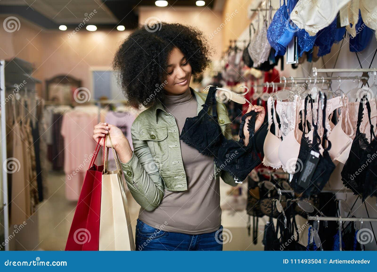Νεολαίες που χαμογελούν την ελκυστική γυναίκα αφροαμερικάνων που επιλέγει το σωστό μέγεθος στηθοδέσμων lingerie στη μπουτίκ κατασ