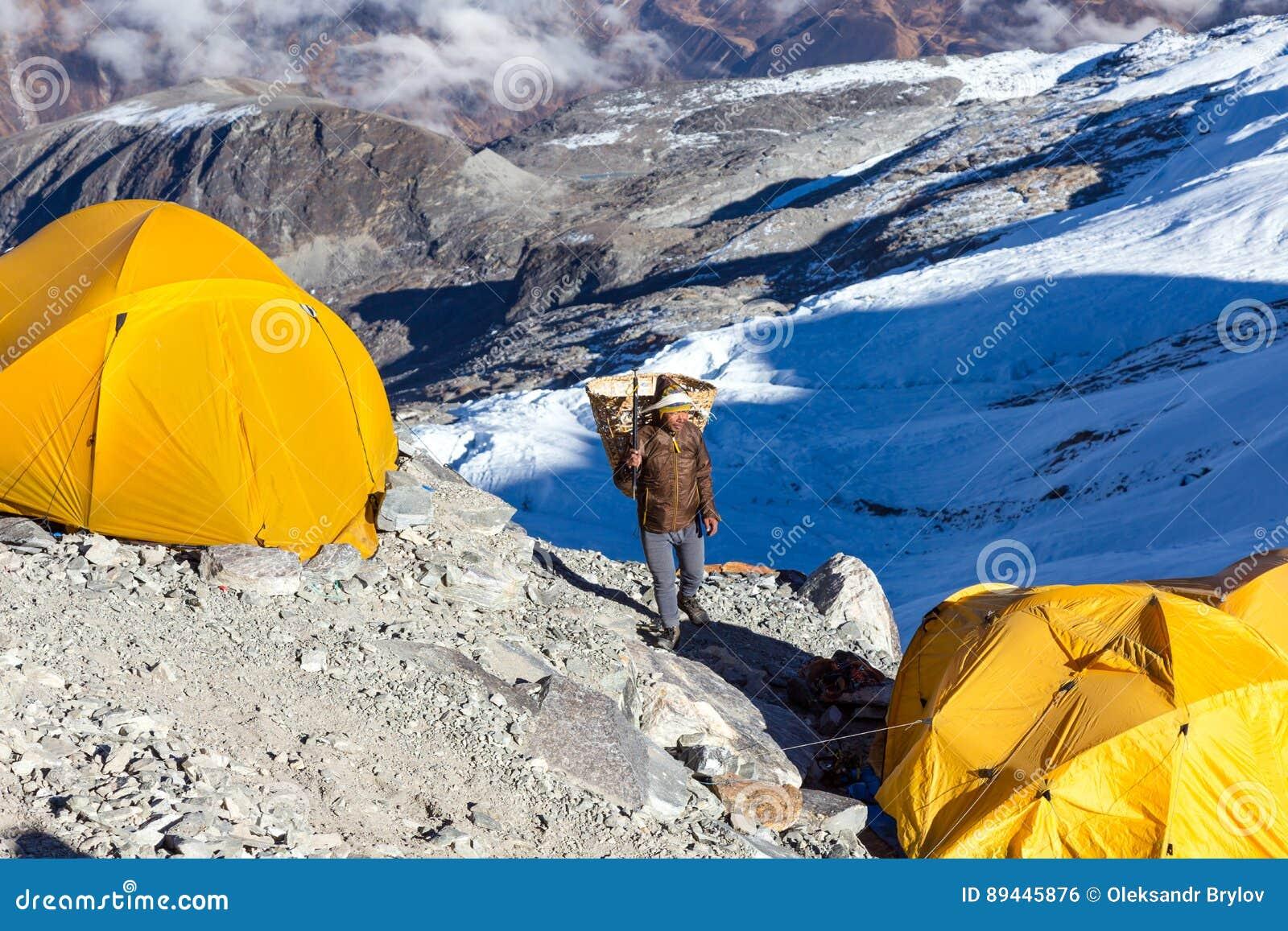 Νεπαλικός αχθοφόρος Sherpa που φέρνει το ψάθινο καλάθι στο στρατόπεδο αποστολής βουνών
