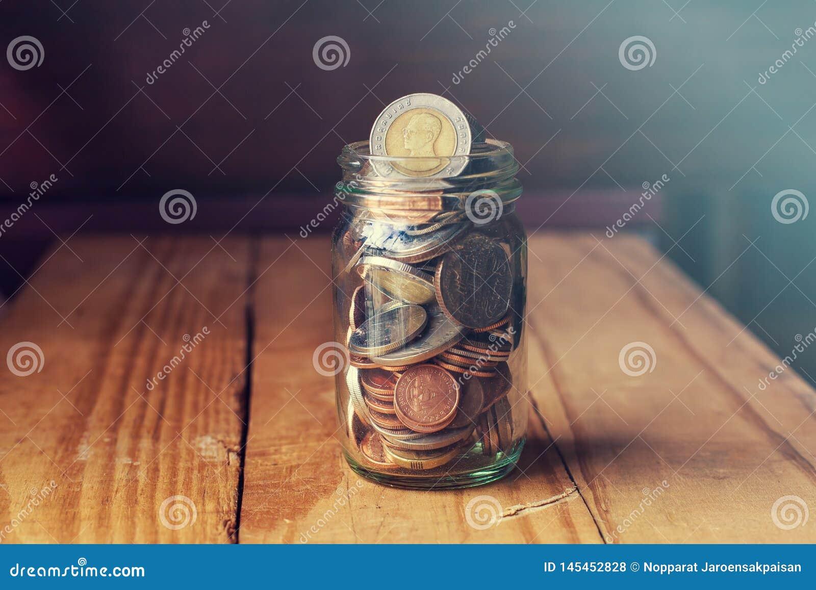 Νομίσματα στο βάζο γυαλιού στον ξύλινο πίνακα, που σώζει την έννοια χρημάτων