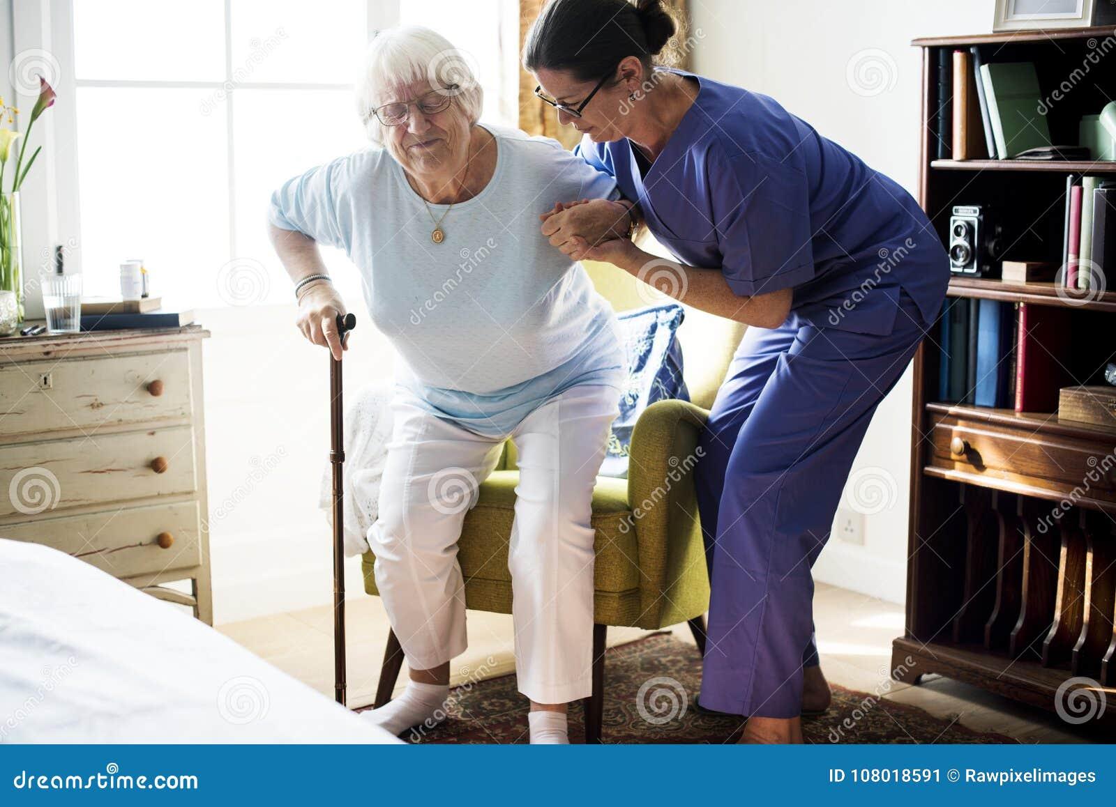 Νοσοκόμα που βοηθά την ανώτερη γυναίκα για να σταθεί