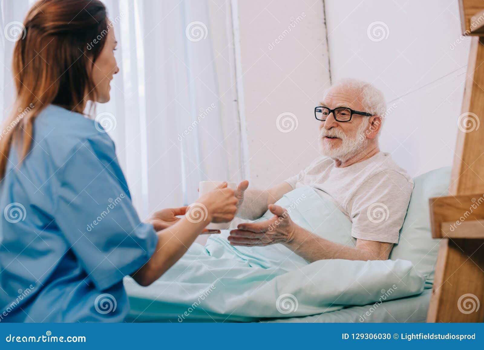 Νοσοκόμα που βοηθά τον ανώτερο ασθενή στο κρεβάτι για να κρατήσει