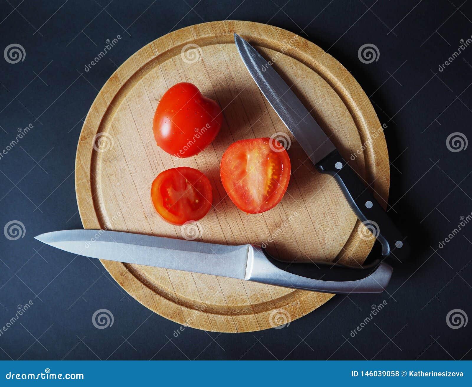 Ντομάτες στο στρογγυλό ξύλινο τέμνοντα πίνακα με τη τοπ άποψη δύο μαχαιριών