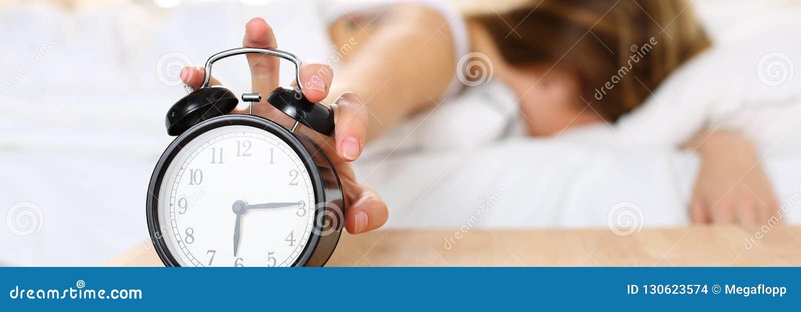 Νυσταλέα νέα γυναίκα που δοκιμάζει το ξυπνητήρι θανάτωσης