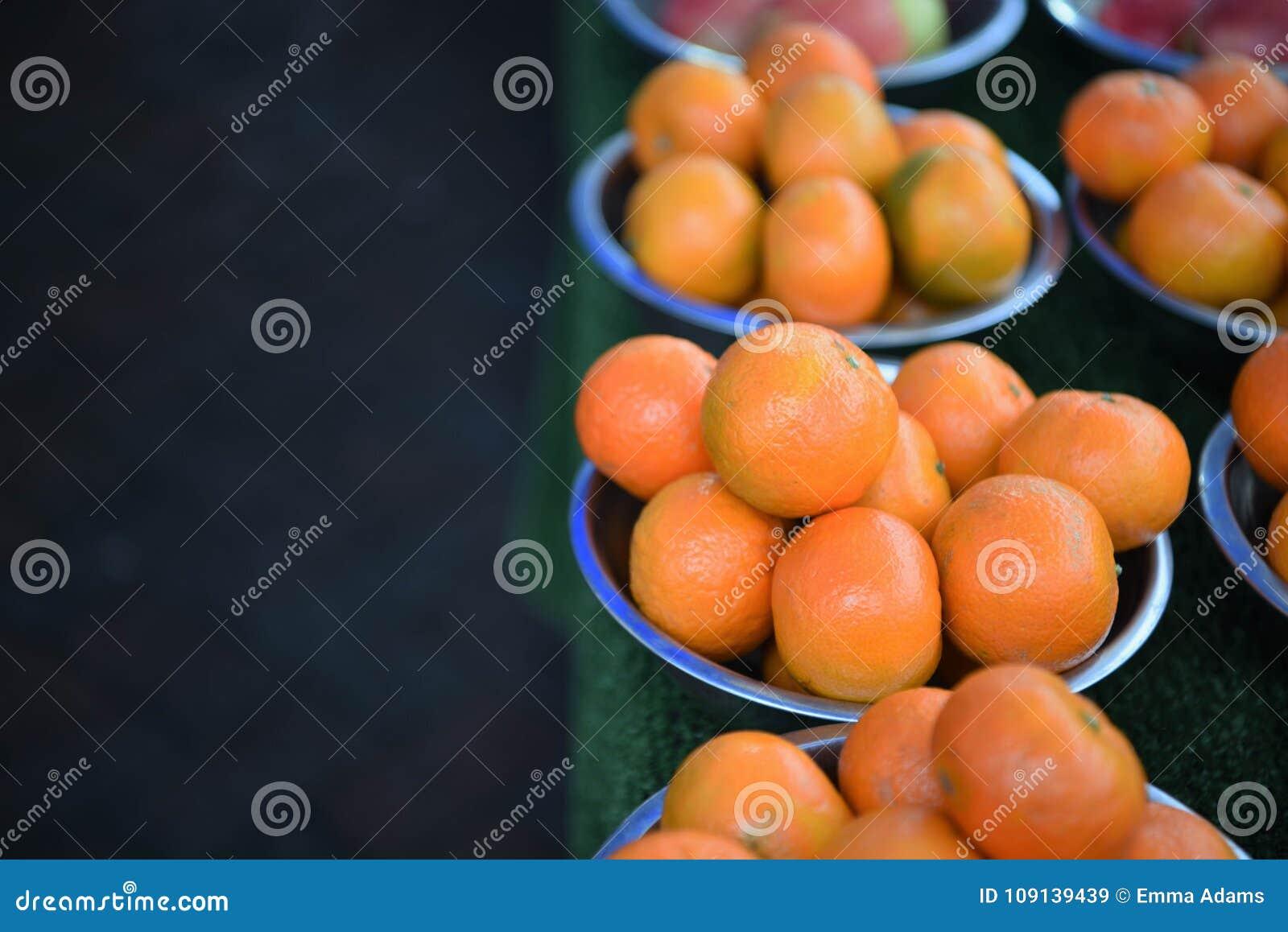 Νωποί καρποί των φωτεινών χρωματισμένων πορτοκαλιών στα κύπελλα με το σκοτεινό υπόβαθρο