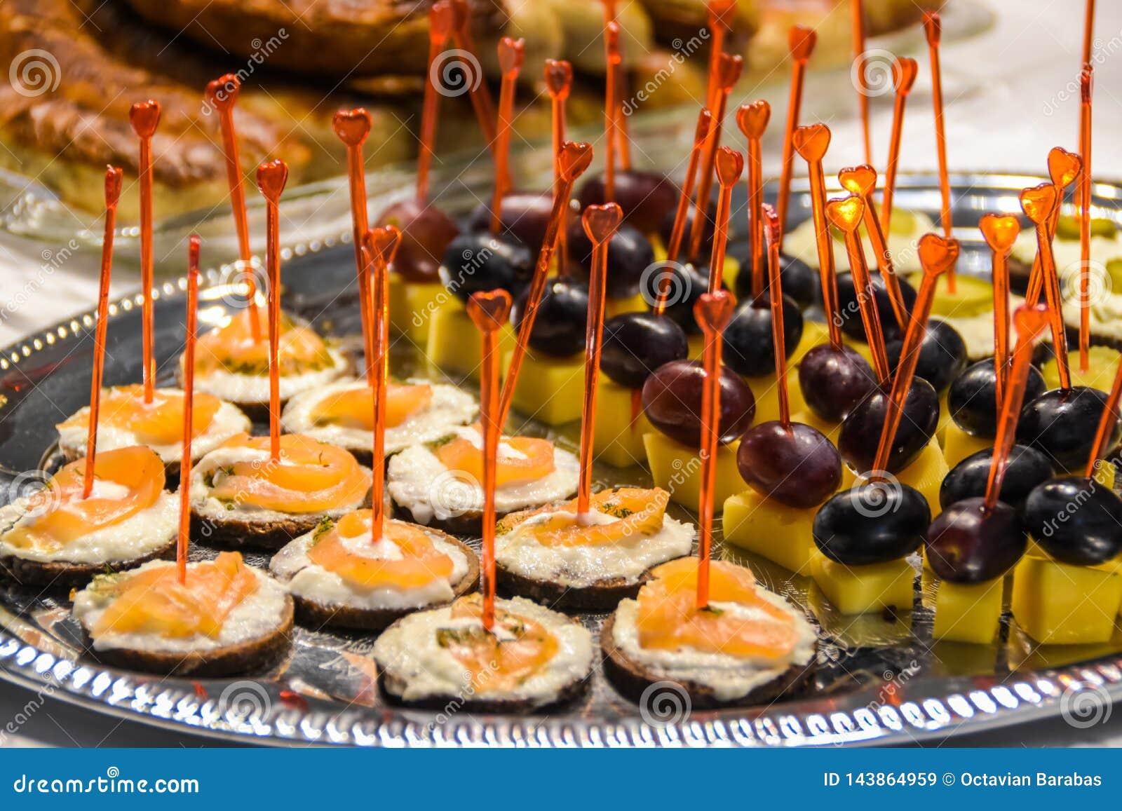 Νόστιμα ορεκτικά με το τυρί και ψάρια και σταφύλια και το τυρί στην ασημένια πιατέλα