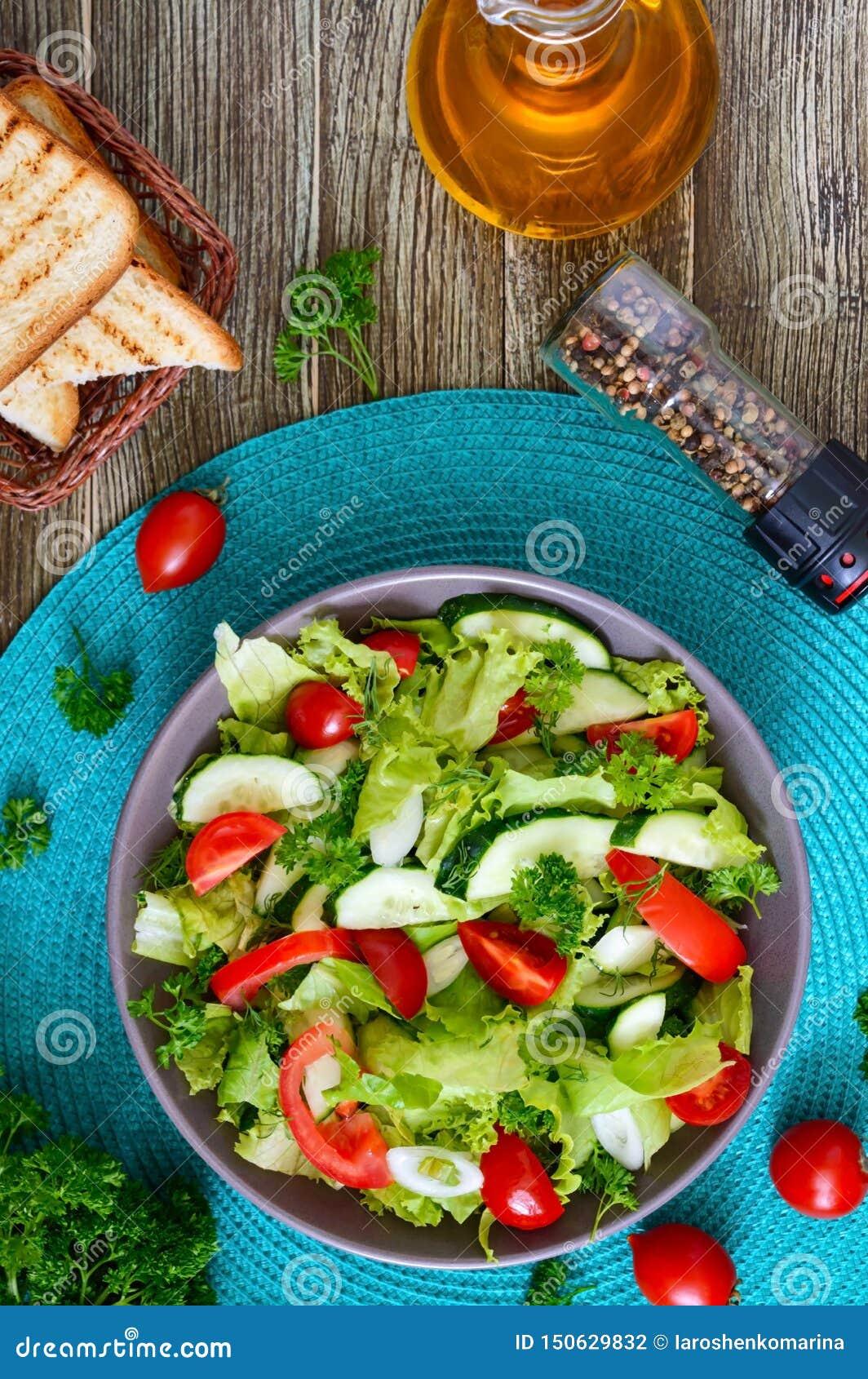 Νόστιμη διαιτητική σαλάτα βιταμινών με τα φρέσκα αγγούρια, ντομάτες, πράσινα Σαλάτα από τα οργανικά λαχανικά r