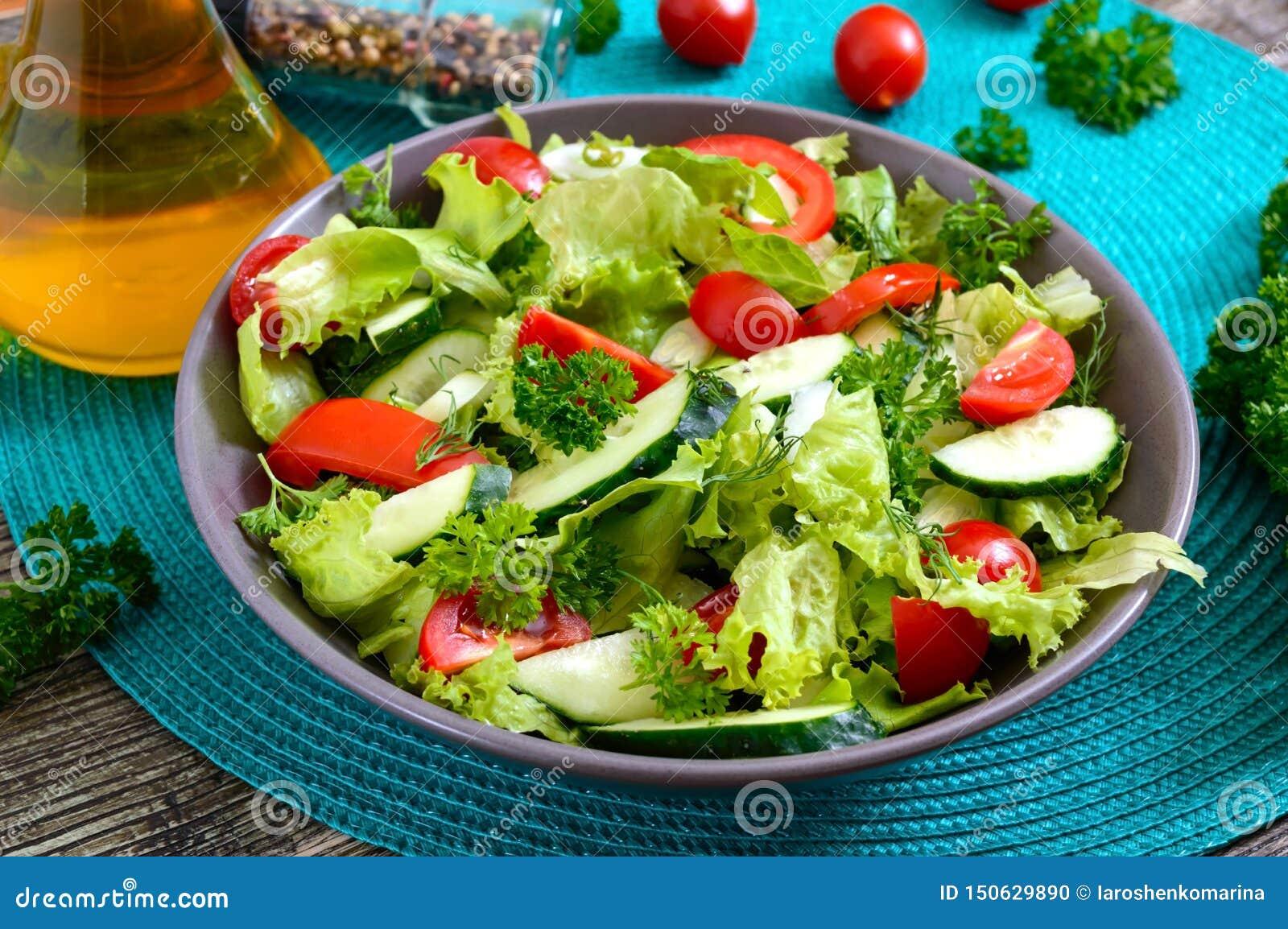 Νόστιμη διαιτητική σαλάτα βιταμινών με τα φρέσκα αγγούρια, ντομάτες, πράσινα Σαλάτα από τα οργανικά λαχανικά