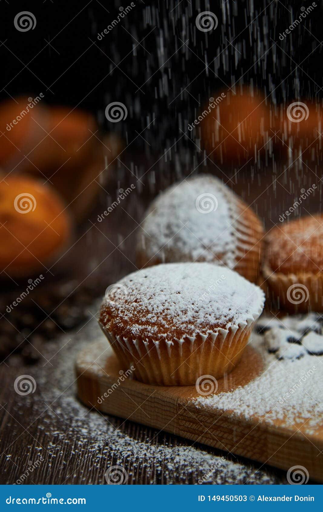 Νόστιμη muffin κινηματογράφηση σε πρώτο πλάνο σε έναν ξύλινο πίνακα που ψεκάζεται με την κονιοποιημένη ζάχαρη, εκλεκτική εστίαση