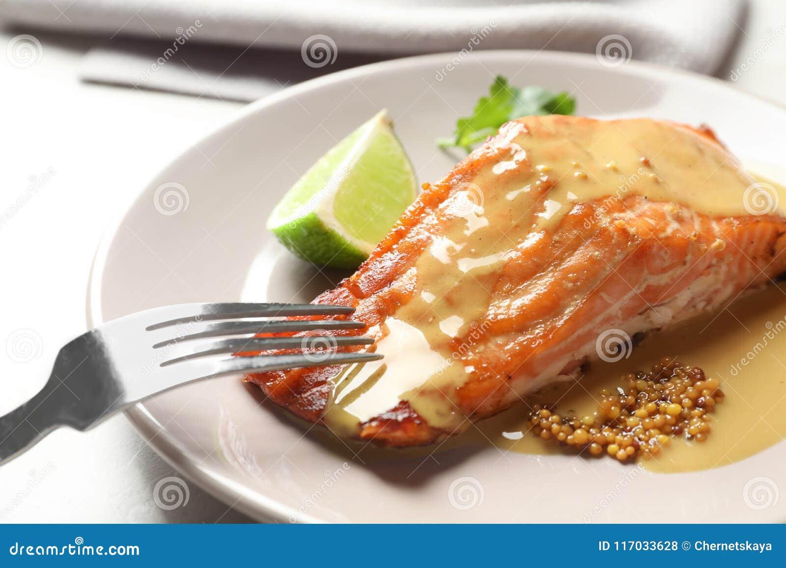 Νόστιμος μαγειρευμένος σολομός με τη μουστάρδα στο πιάτο