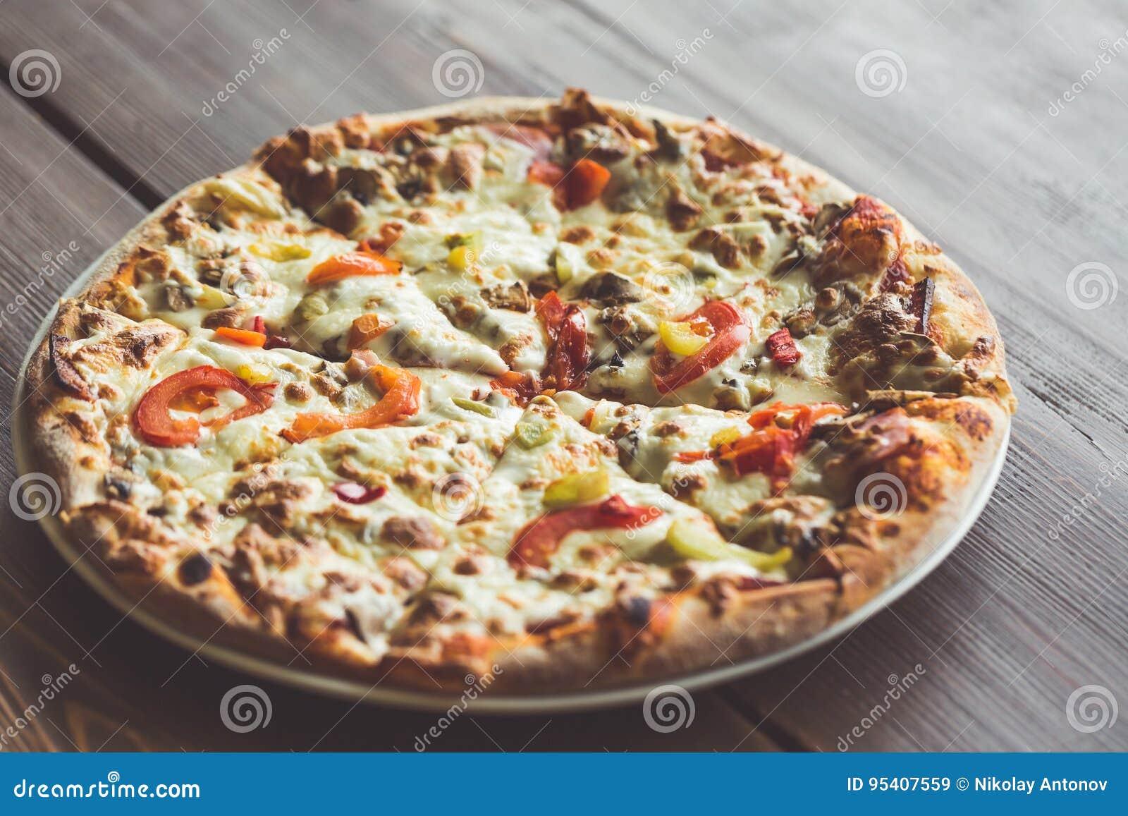 Νόστιμος στενός επάνω πιτσών στο πιάτο και τον ξύλινο πίνακα Πίτσα με το κρεμμύδι, τις ντομάτες, το τυρί, το κρέας και το πιπέρι
