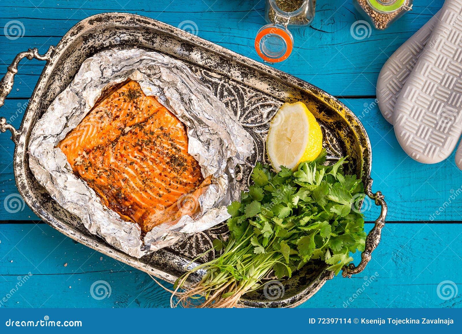 Νόστιμος ψημένος σολομός ψαριών στο φύλλο αλουμινίου στον μπλε πίνακα, τοπ άποψη