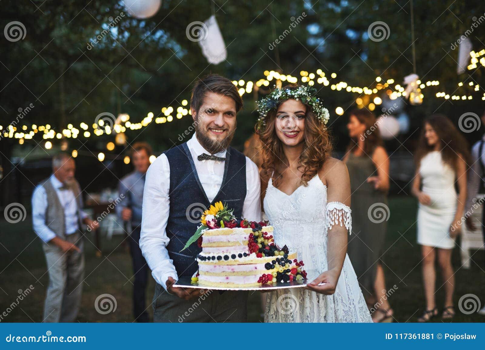 Νύφη και νεόνυμφος που κρατούν ένα κέικ στη δεξίωση γάμου έξω στο κατώφλι