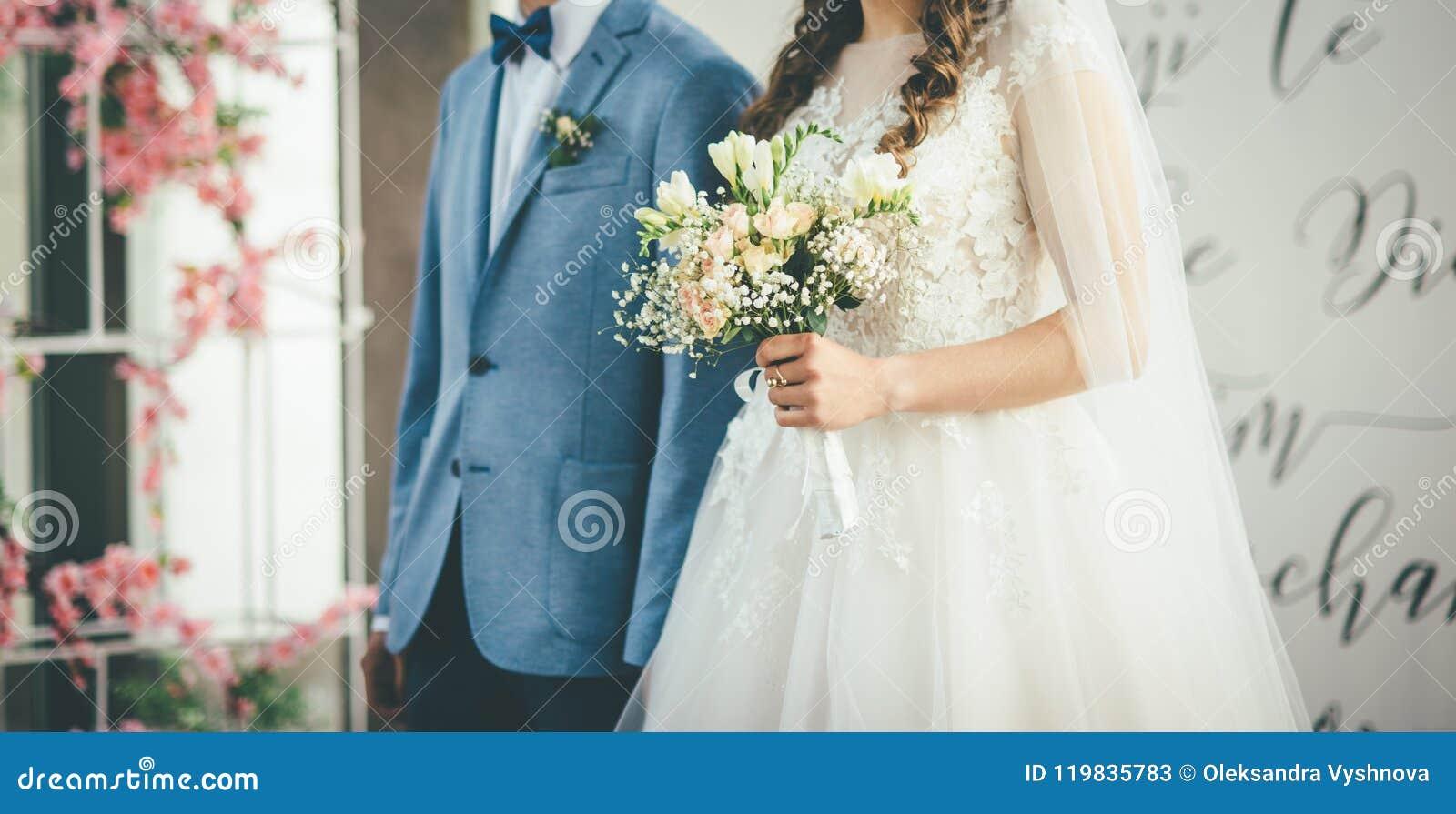 Νύφη και νεόνυμφος που περπατούν μαζί με την ανθοδέσμη στα χέρια