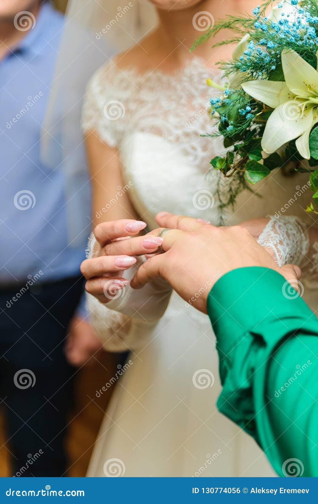 Νύφη και νεόνυμφος που φορούν τα γαμήλια δαχτυλίδια