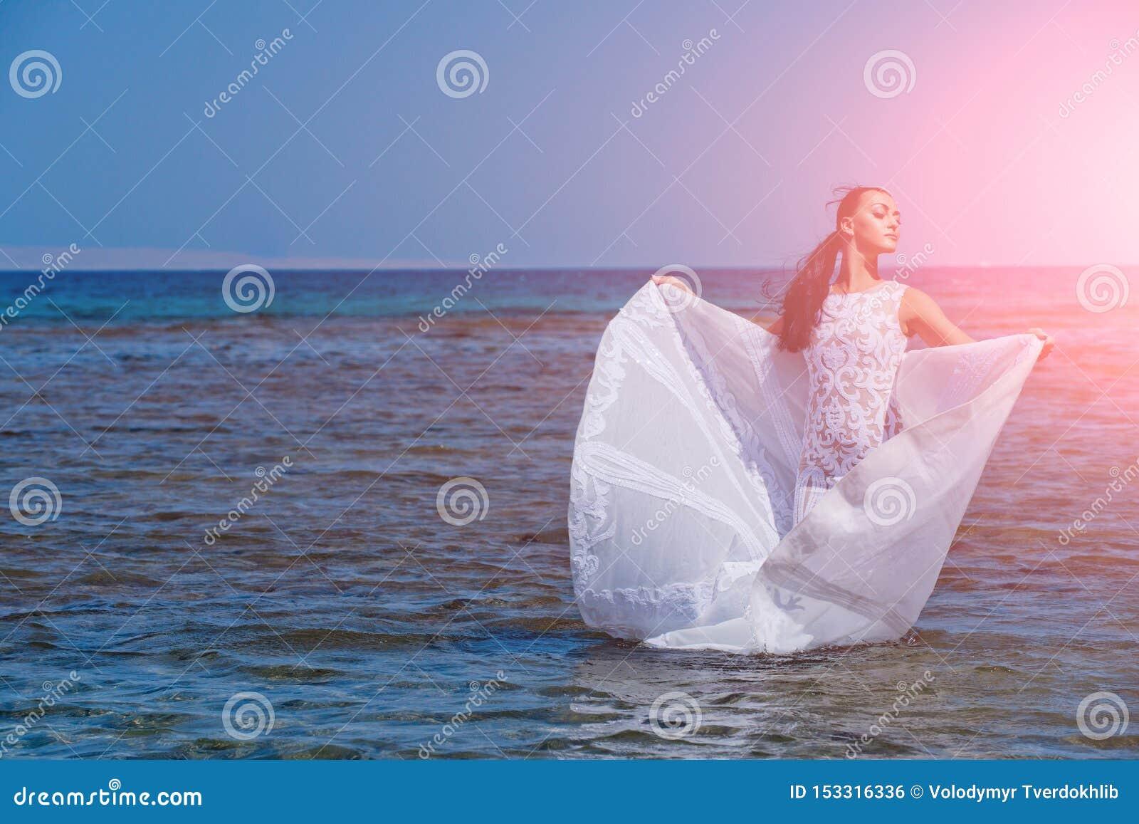 Νύφη την ηλιόλουστη θερινή ημέρα στο μπλε νερό