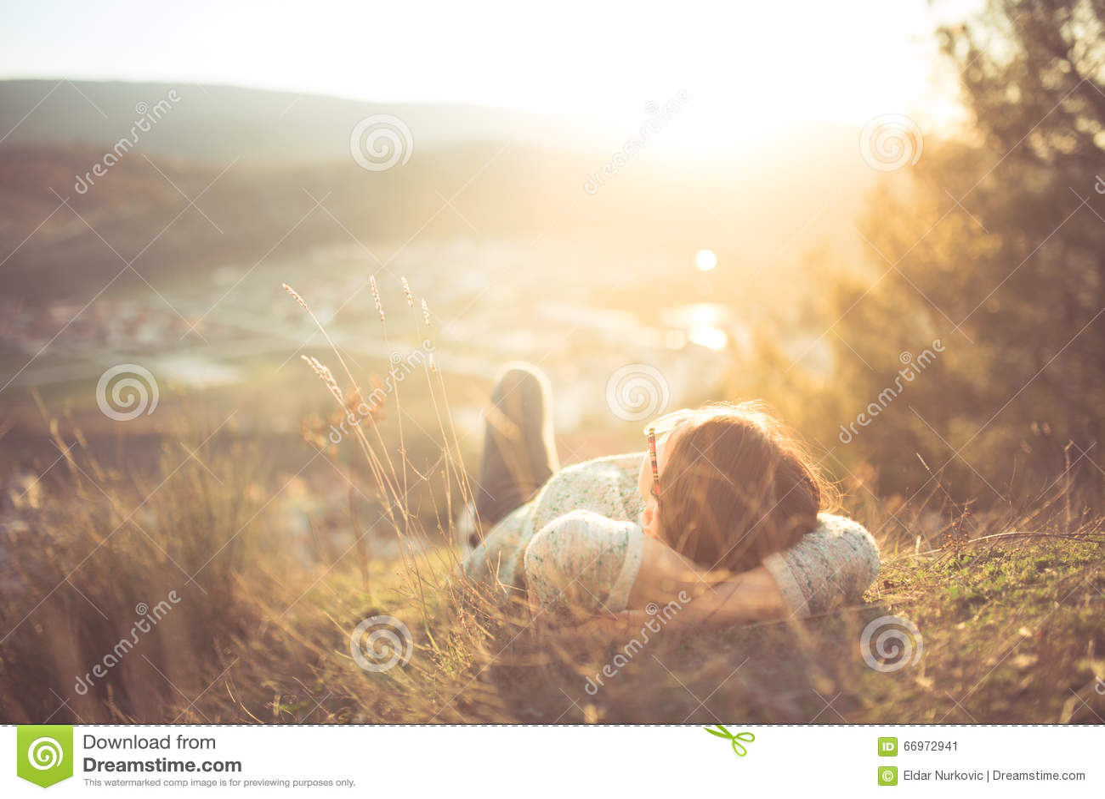 Ξένοιαστη ευτυχής γυναίκα που βρίσκεται στο πράσινο λιβάδι χλόης πάνω από τον απότομο βράχο ακρών βουνών που απολαμβάνει τον ήλιο