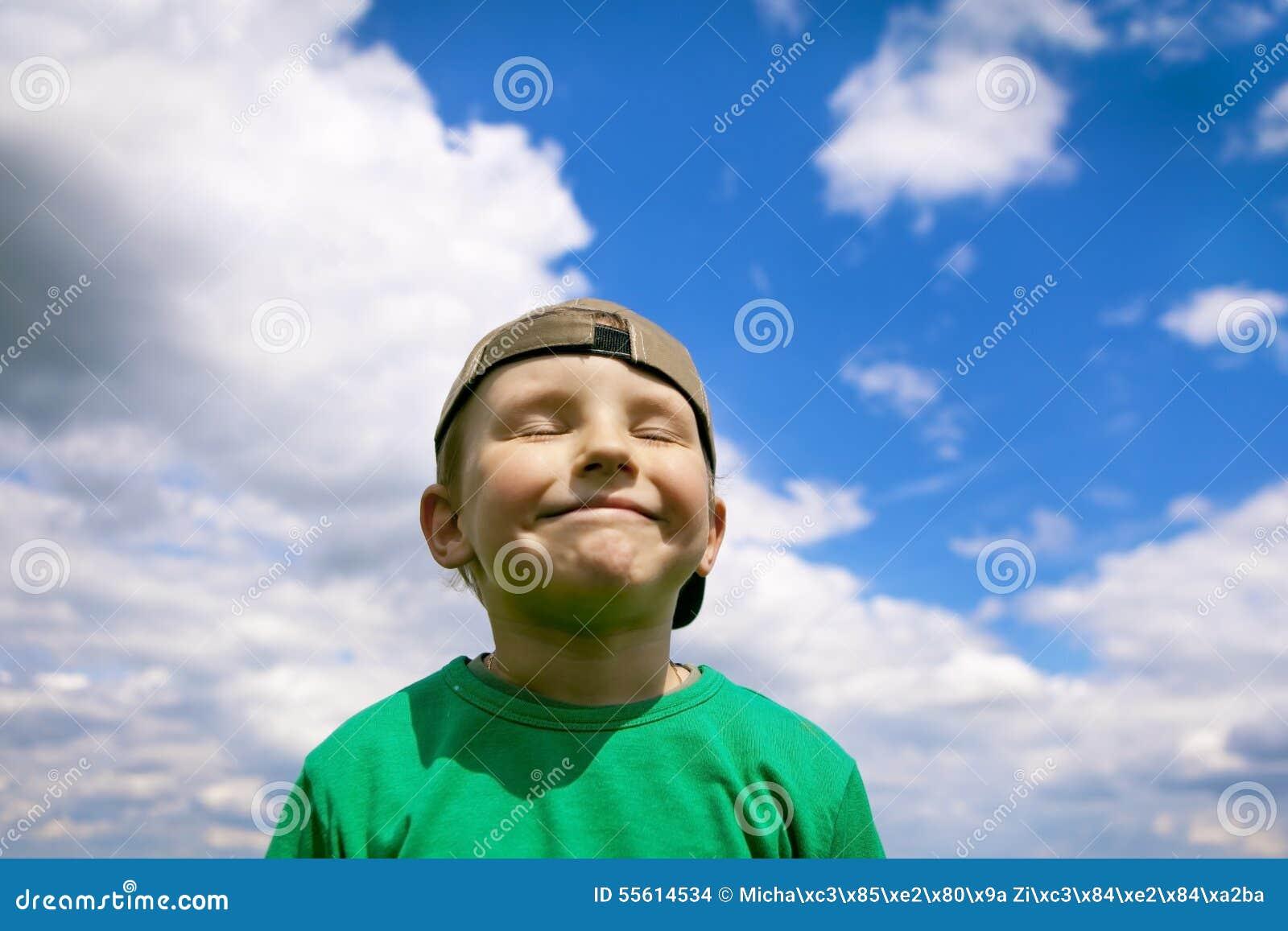 Ξένοιαστο, χαμογελώντας αγόρι στο μπλε ουρανό και λευκά σύννεφα Υπερήφανος και ευτυχής με τον, μια γοητεία λίγο σκανταλιάρικο παι